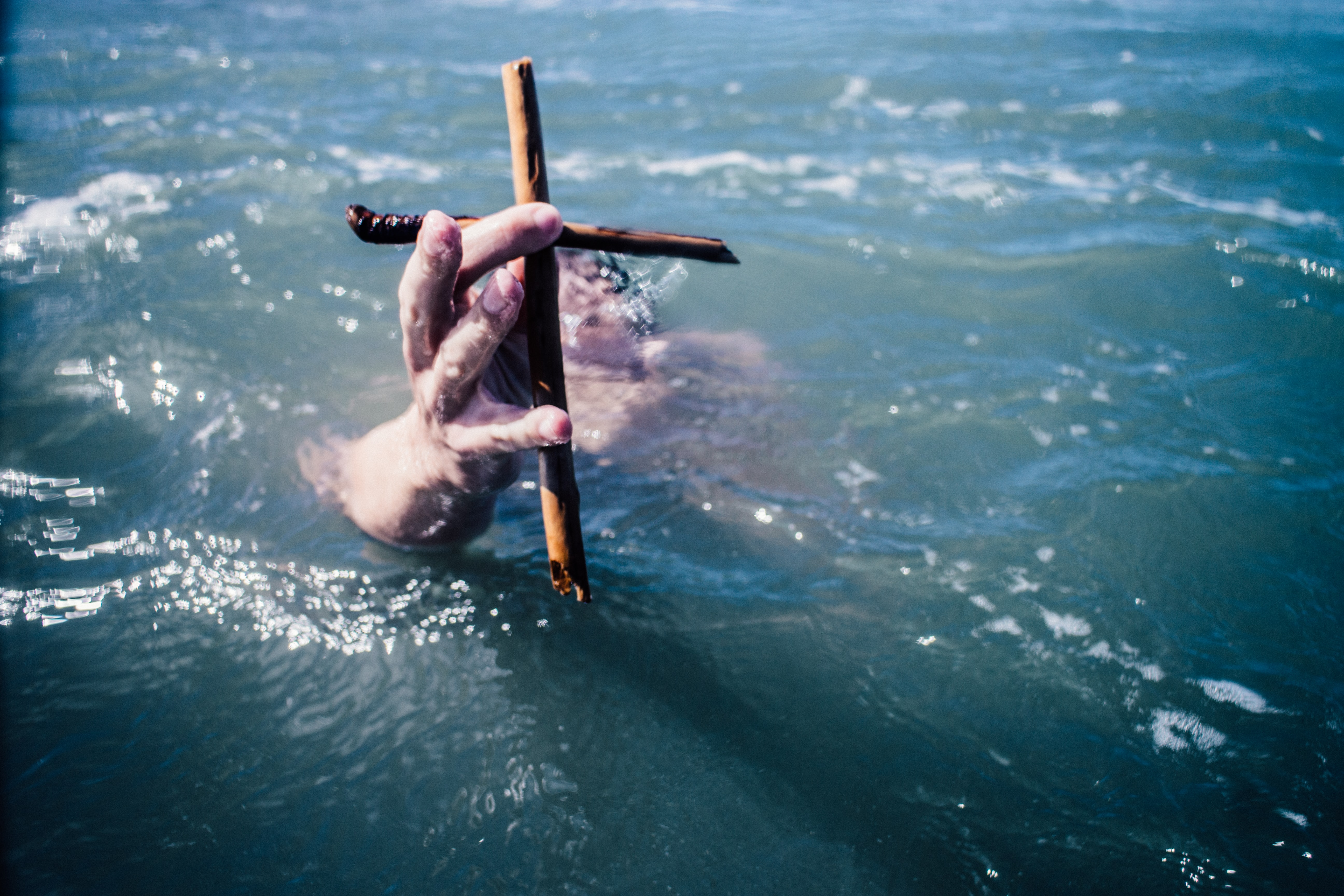 person under water holding brown wooden cross above water at daytime