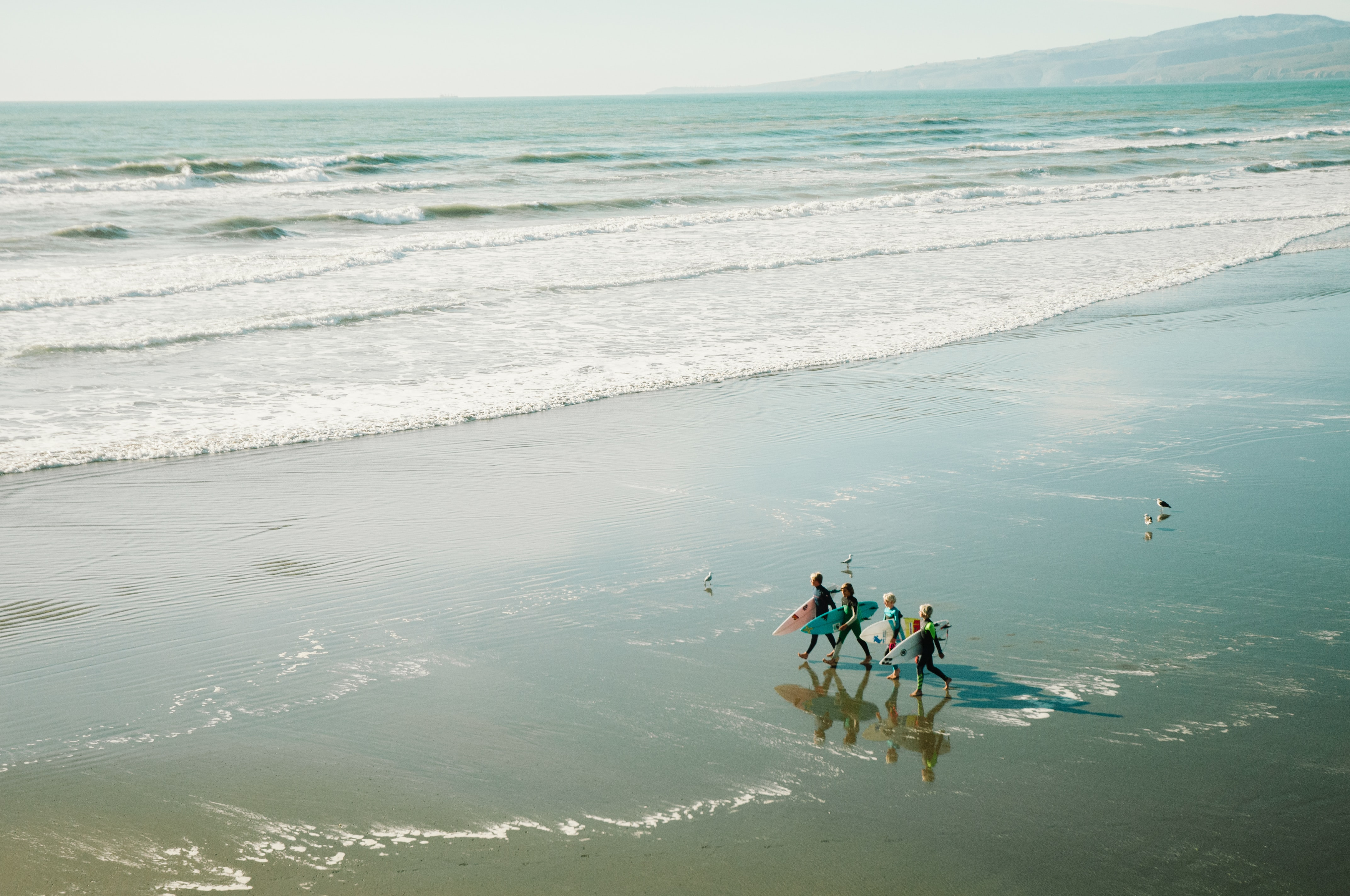 Four surfers walk along the beach with their brightly colored surfboards.