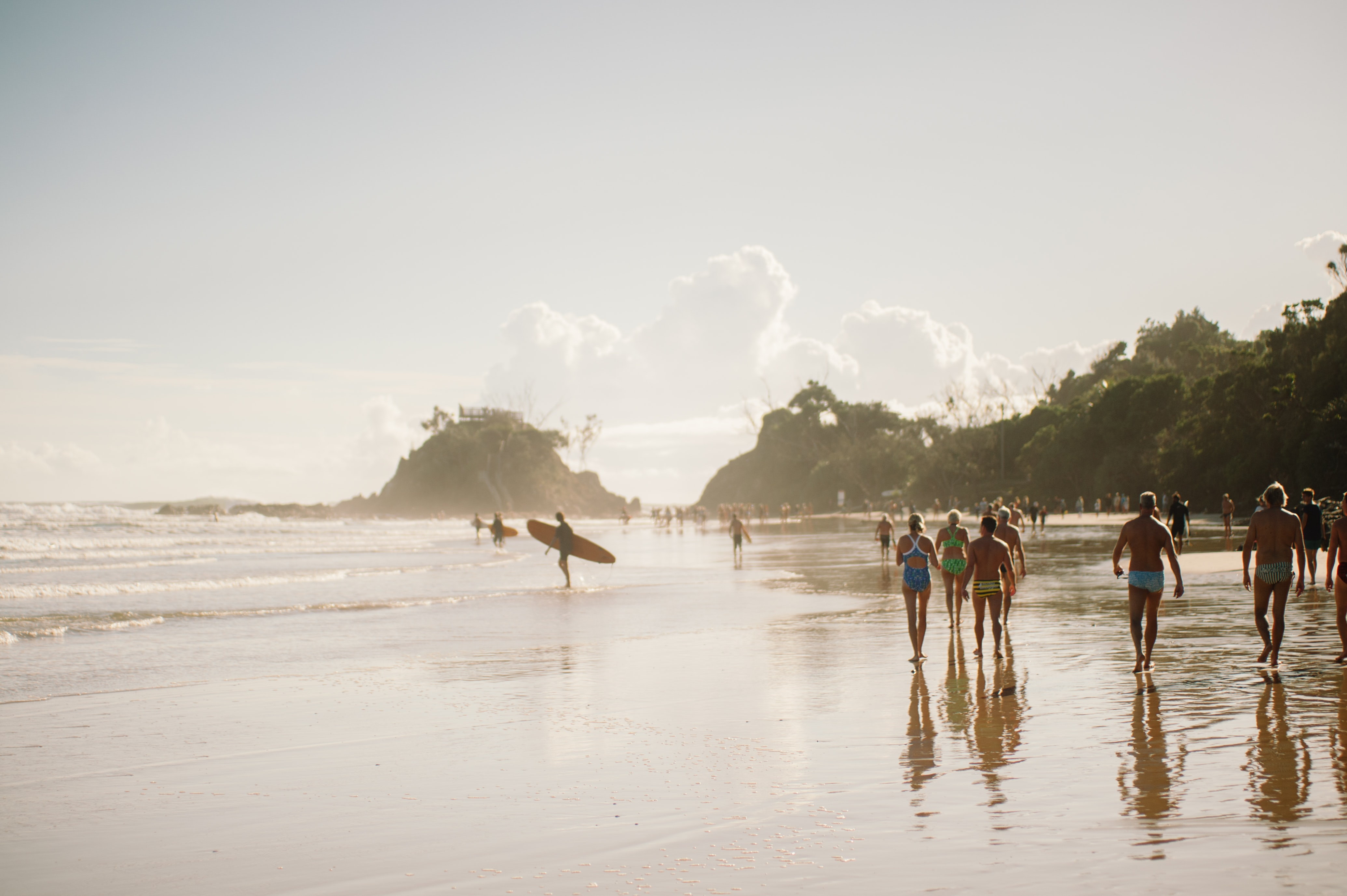 Beach goers walking down the tree-lined shore as surfers carry their boards into the sea at Byron Bay