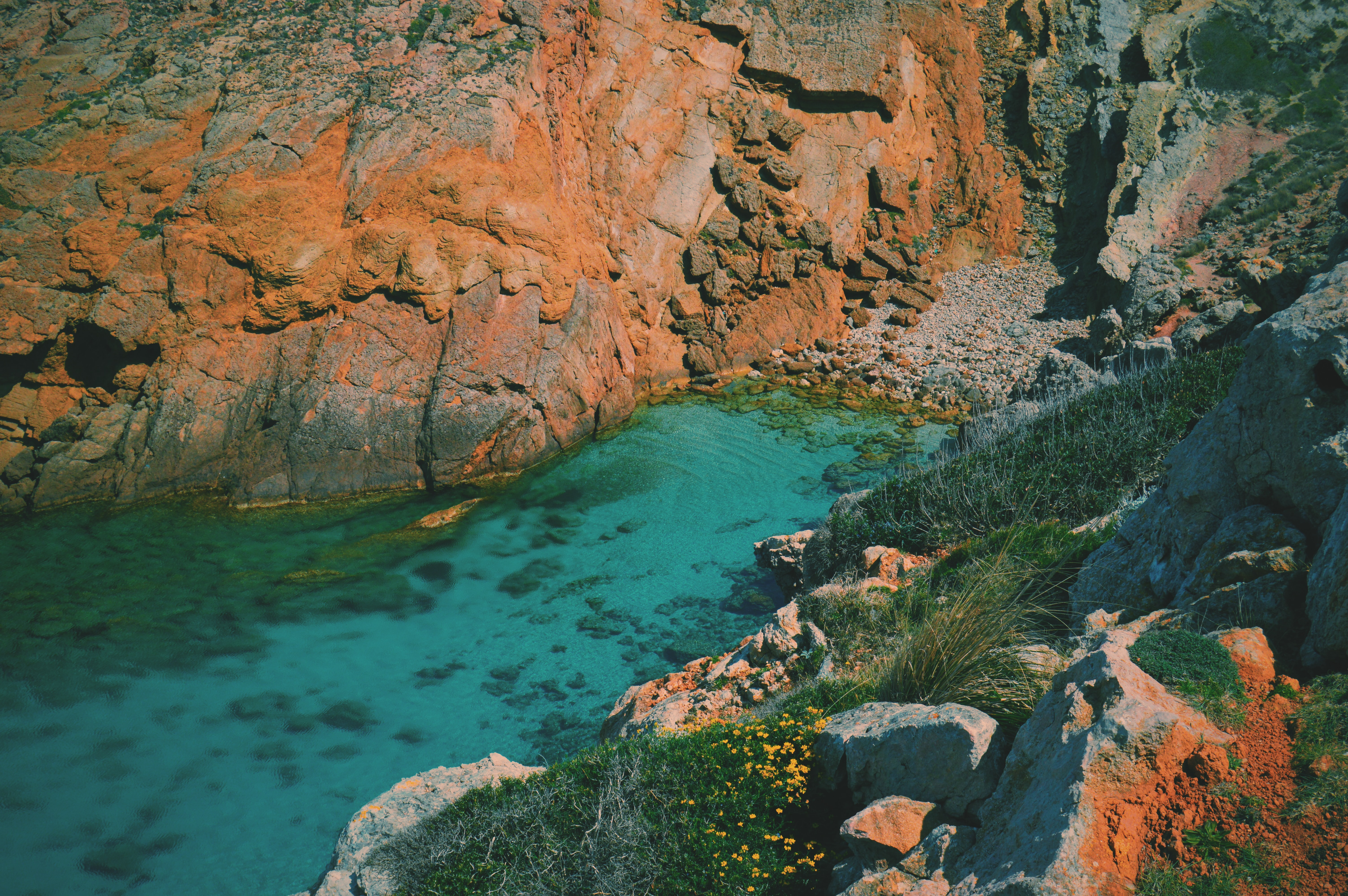 Source of a clear blue river surrounded by red rocky cliffs in Arenal d'en Castell