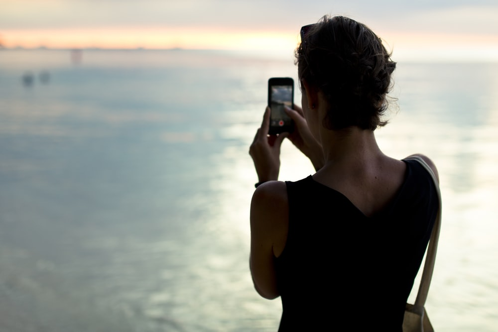 woman taking photo of body of water