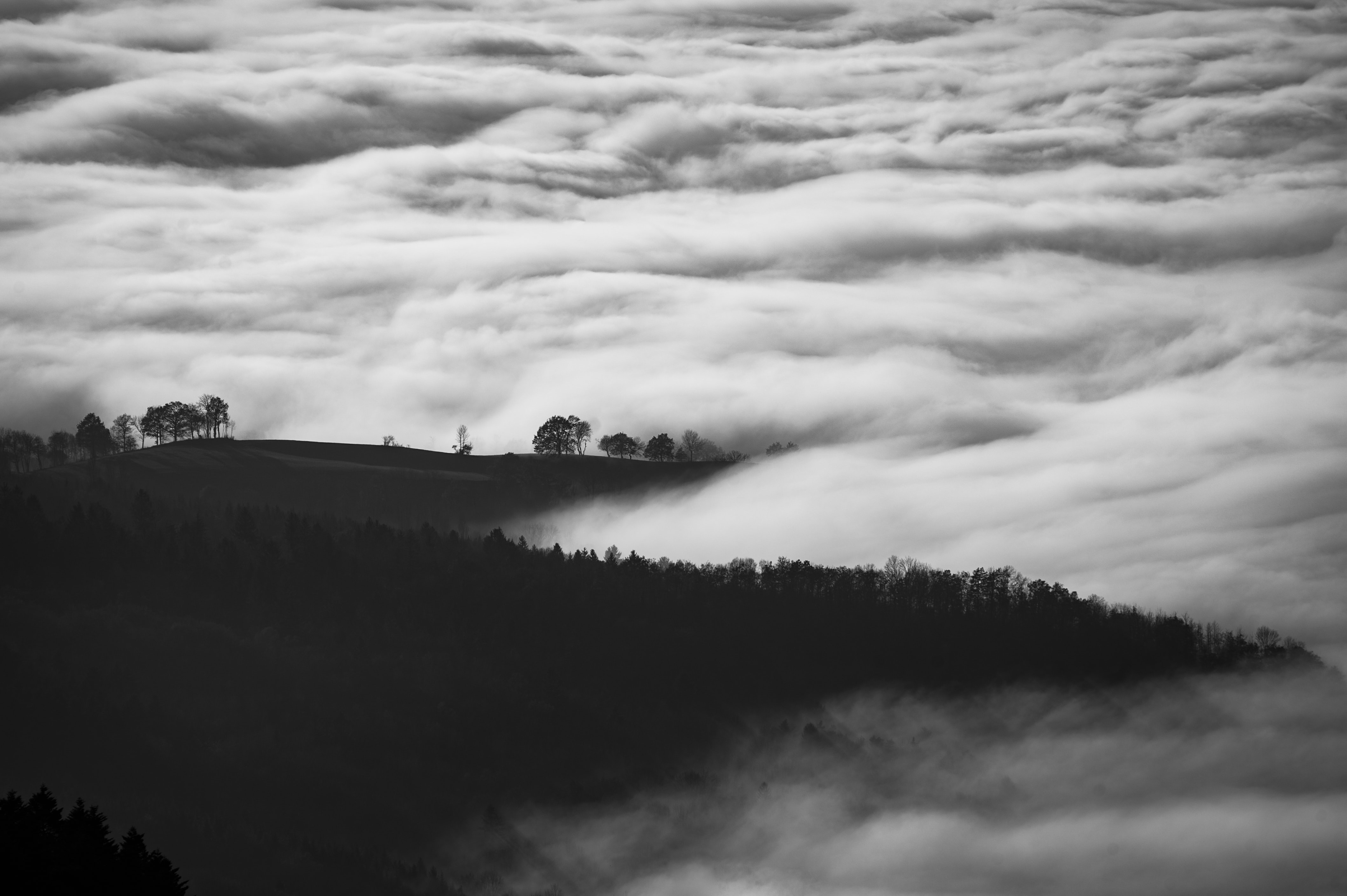 A desaturated shot of clouds enveloping hills in the countryside