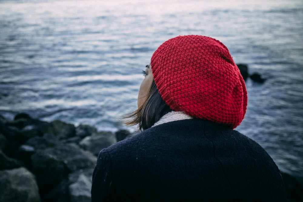 woman in black jacket and red knit cap standing on rocky shore during daytime