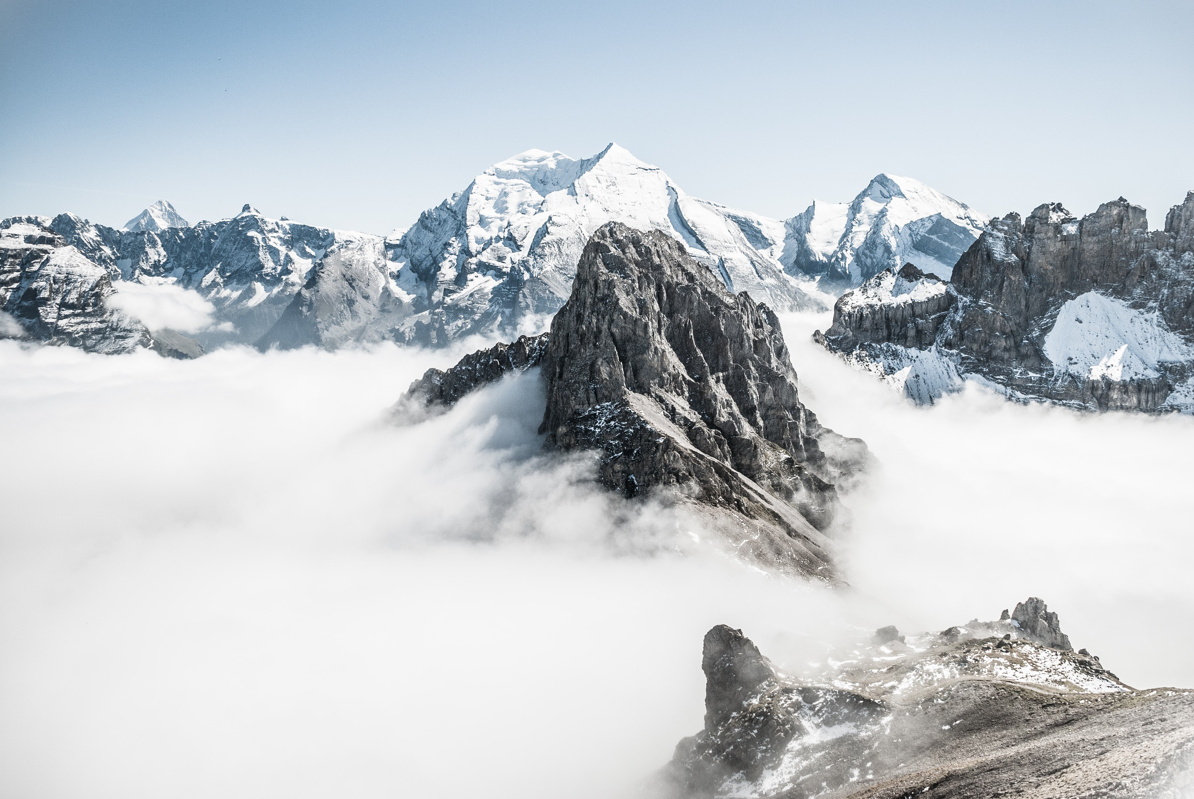 Snowy mountain tops cut through an expanse of clouds