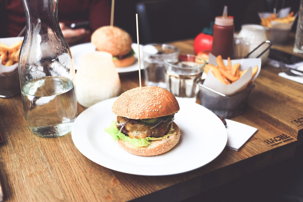 burger patty on plate served with fries and water bottle