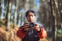 man holding camera taking a photo