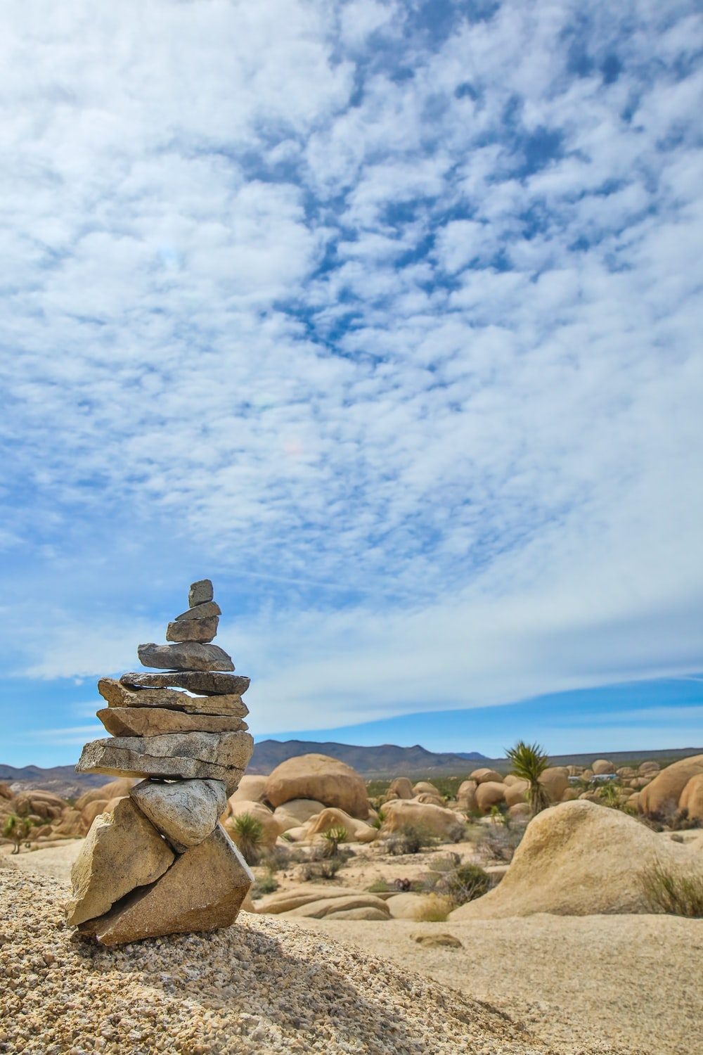 stack of balance stones under white clouds