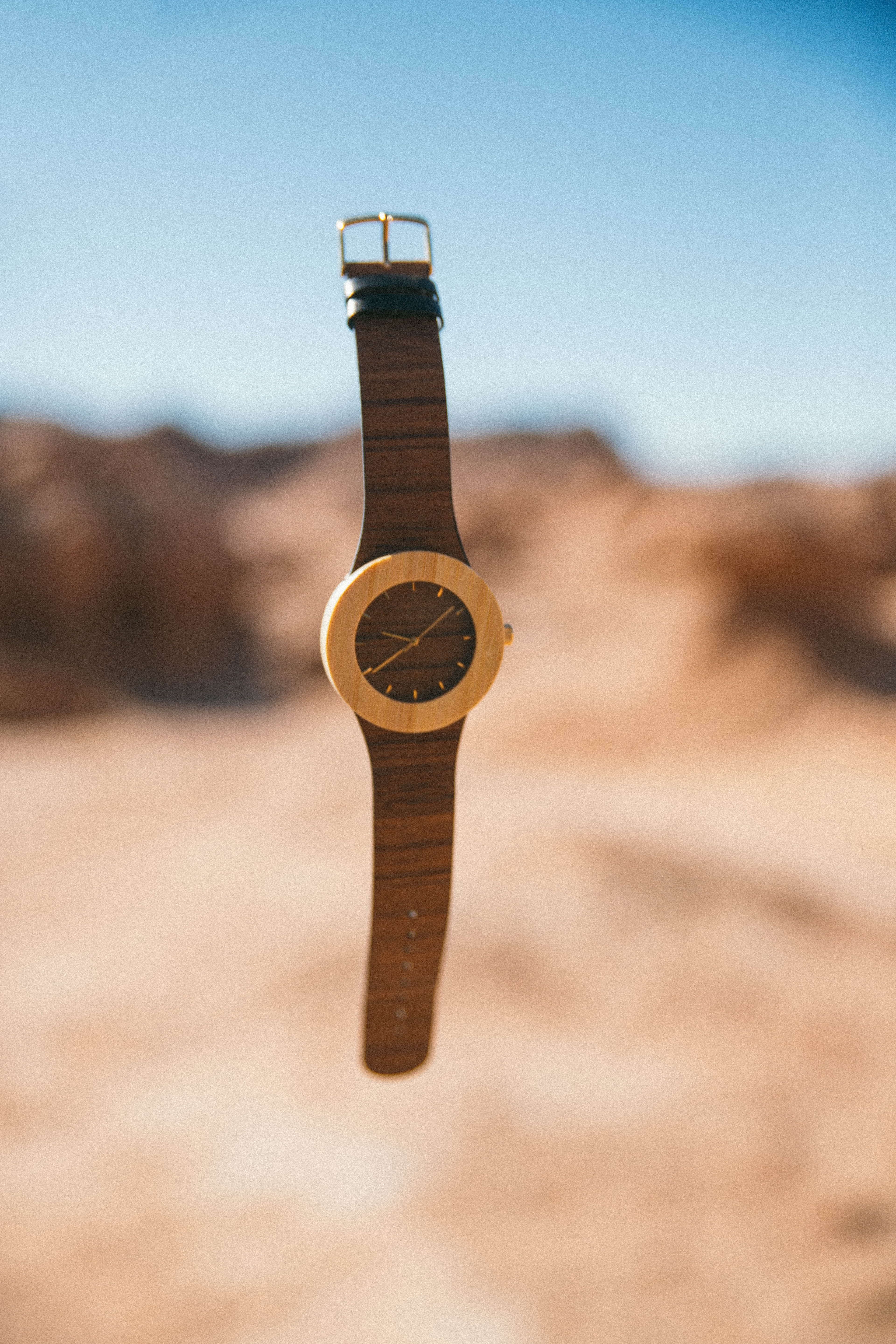 An elegant watch floating in the air above a desert