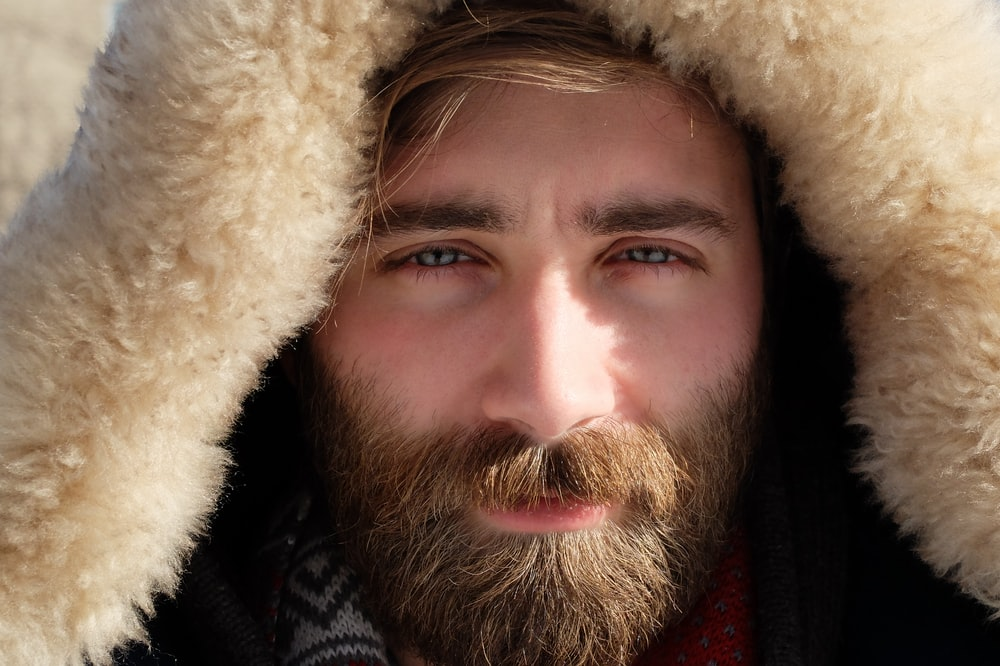man covered by beige fur textile
