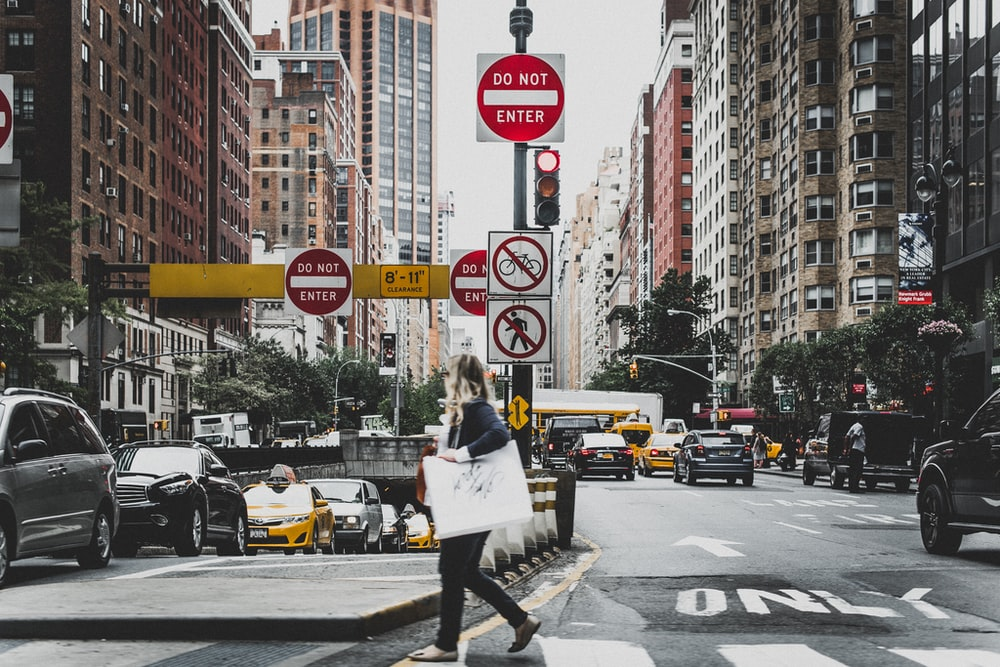 woman walking on road near cars