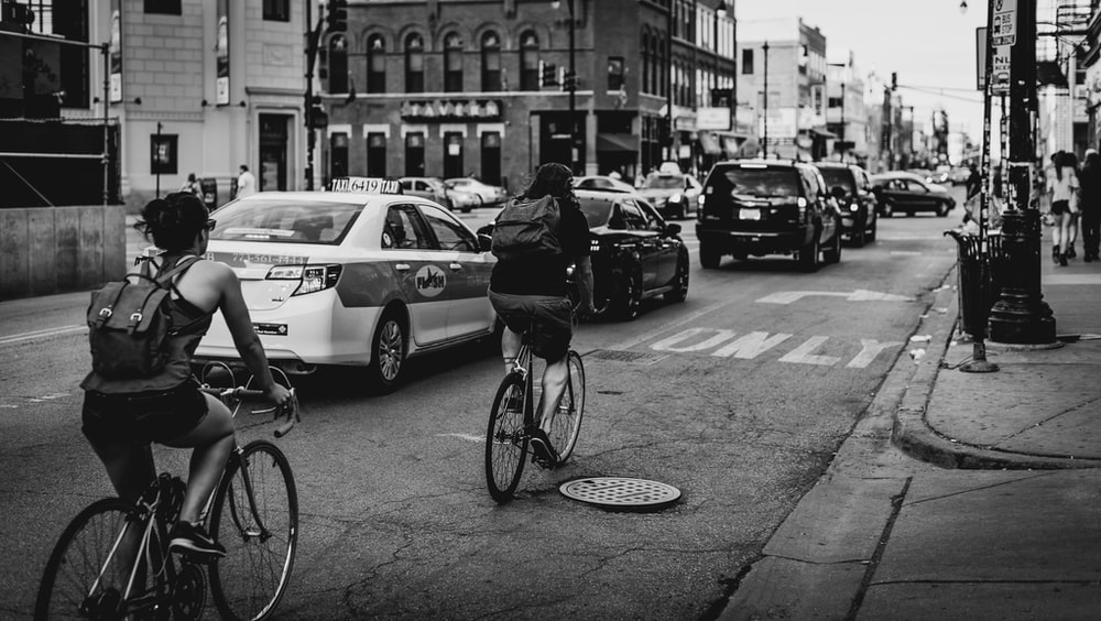 grayscale photo of two person riding bicycle on road