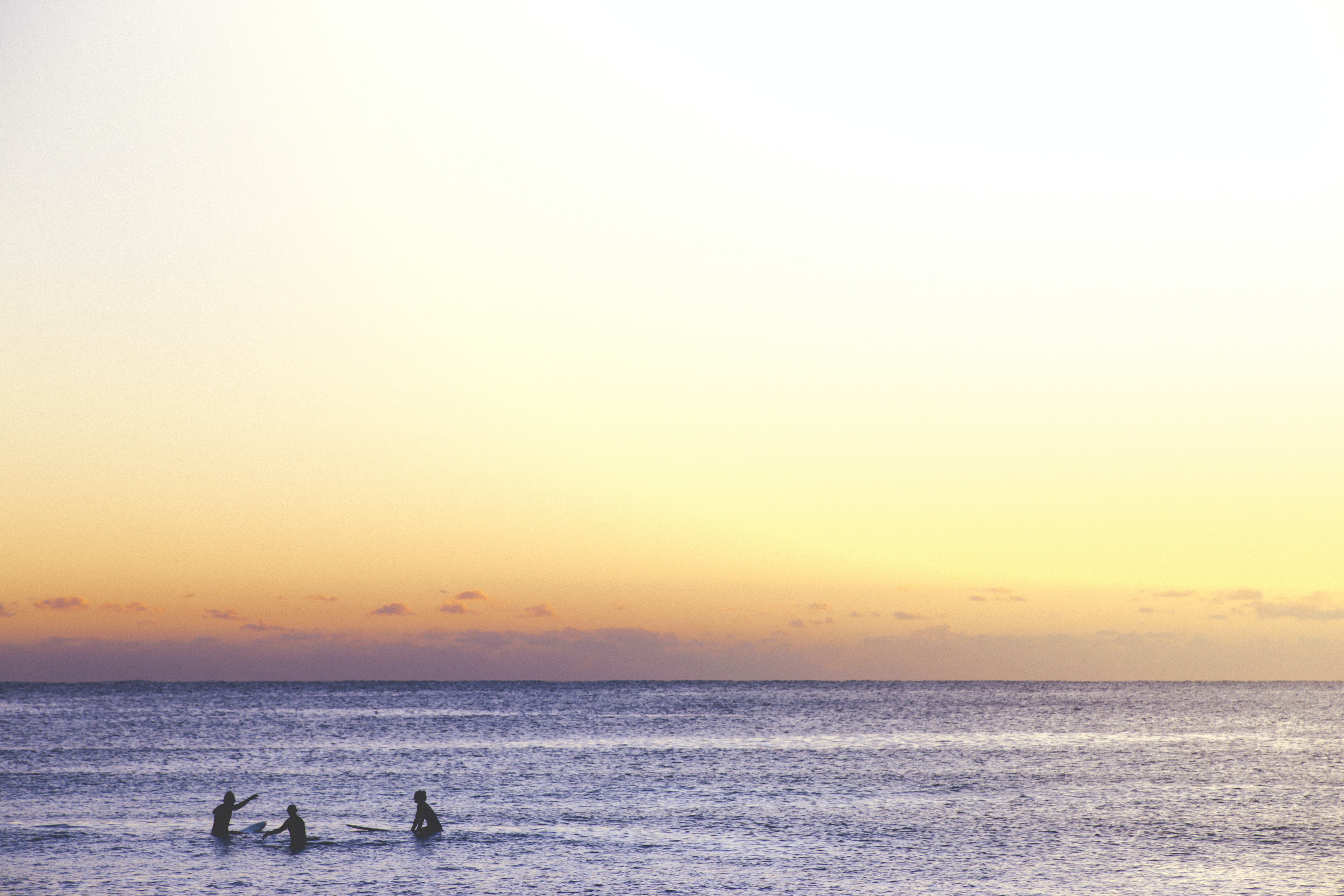 3 people in the calm, shallow sea at Sydney Beach, beneath a beautiful orange and purple sunset sky