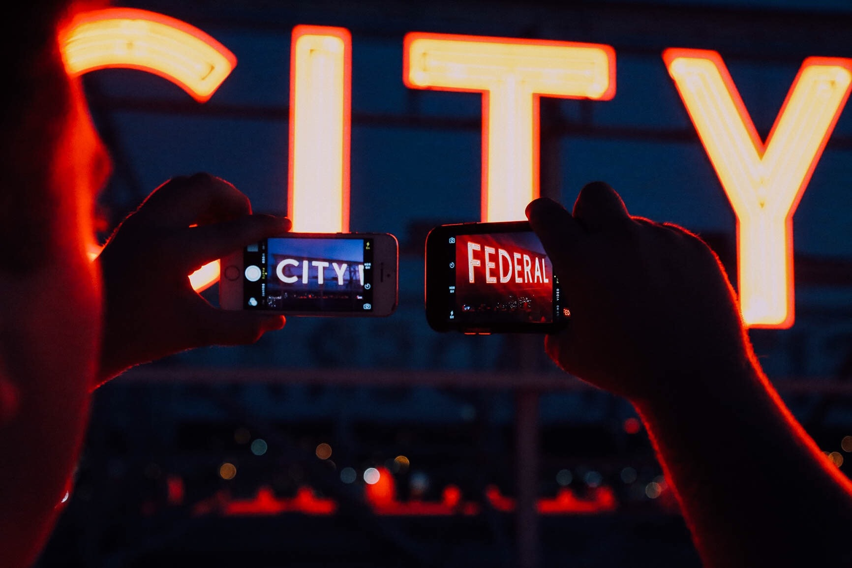 "A man takes the photos of the neon signs ""City"" and ""Federal"" with two phones."