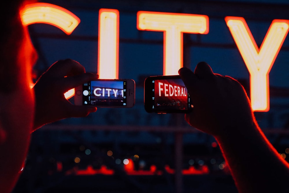 minimalist photography of person taking pictures of City Federal signages