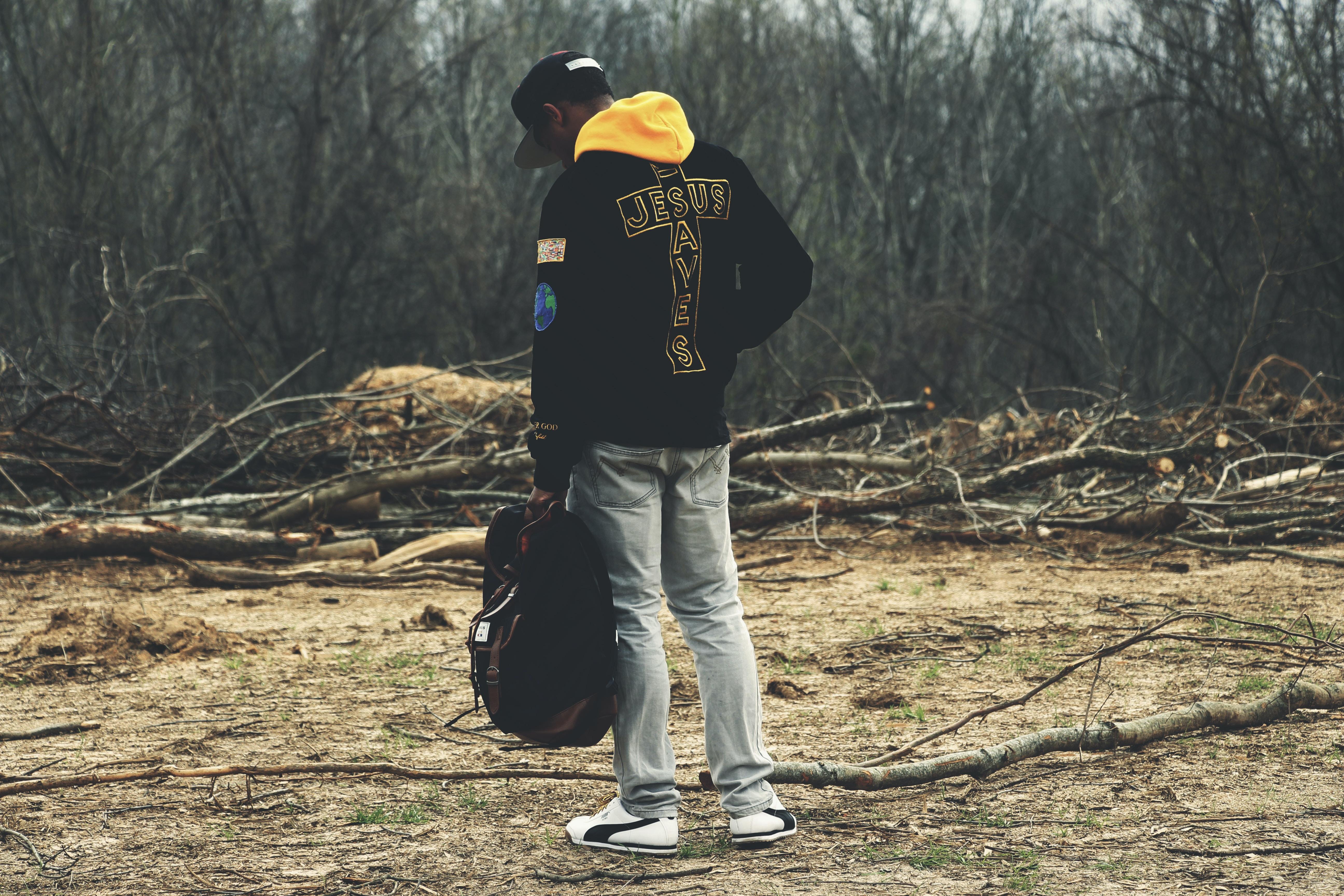 man in gray denim pants and black hoodie holding bag looking down
