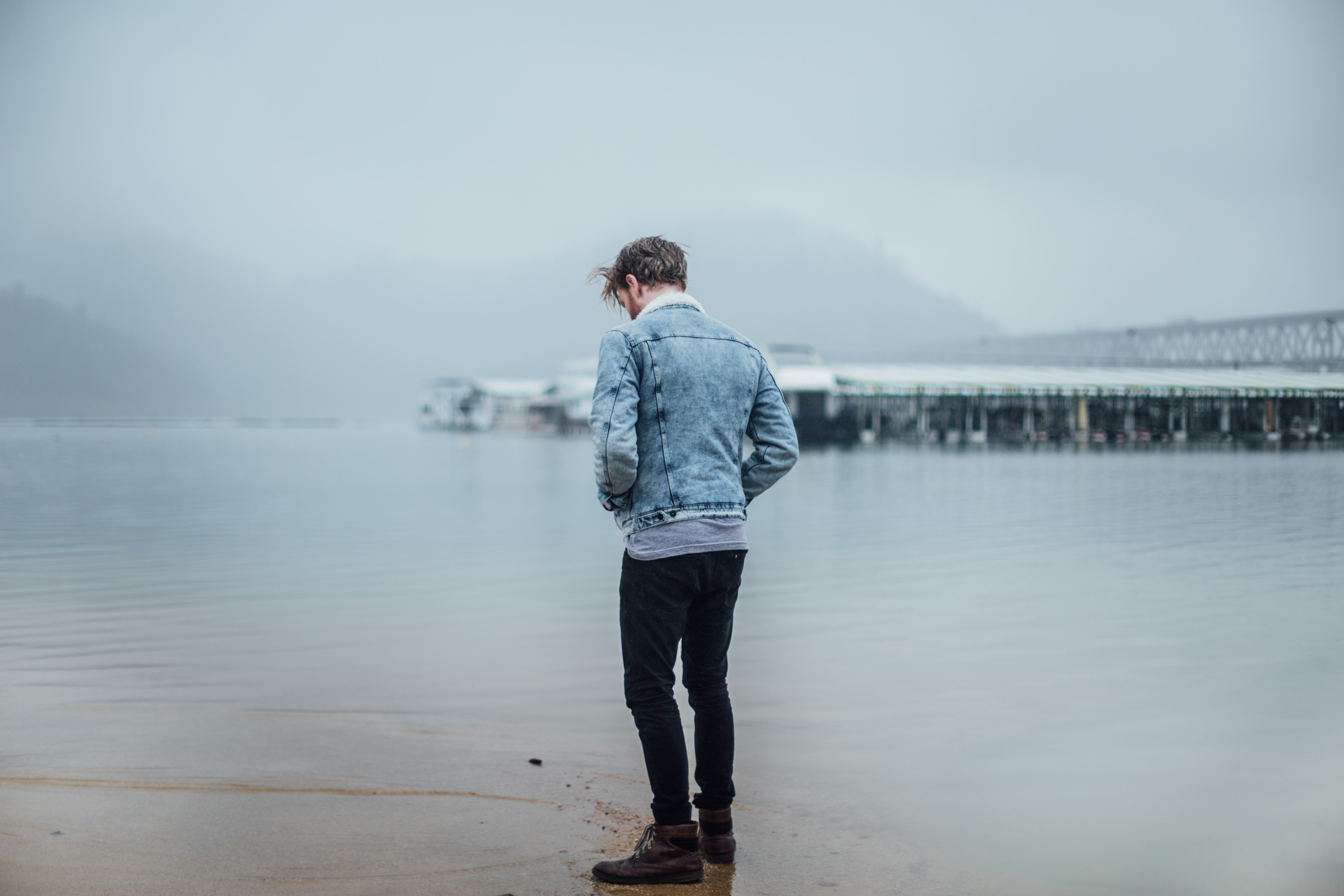 man in blue denim jacket standing on shore