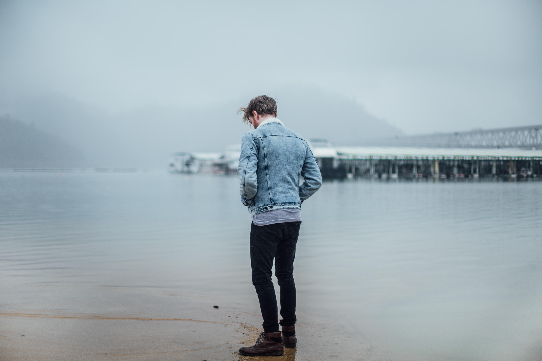man in blue denim jacket standing on shore