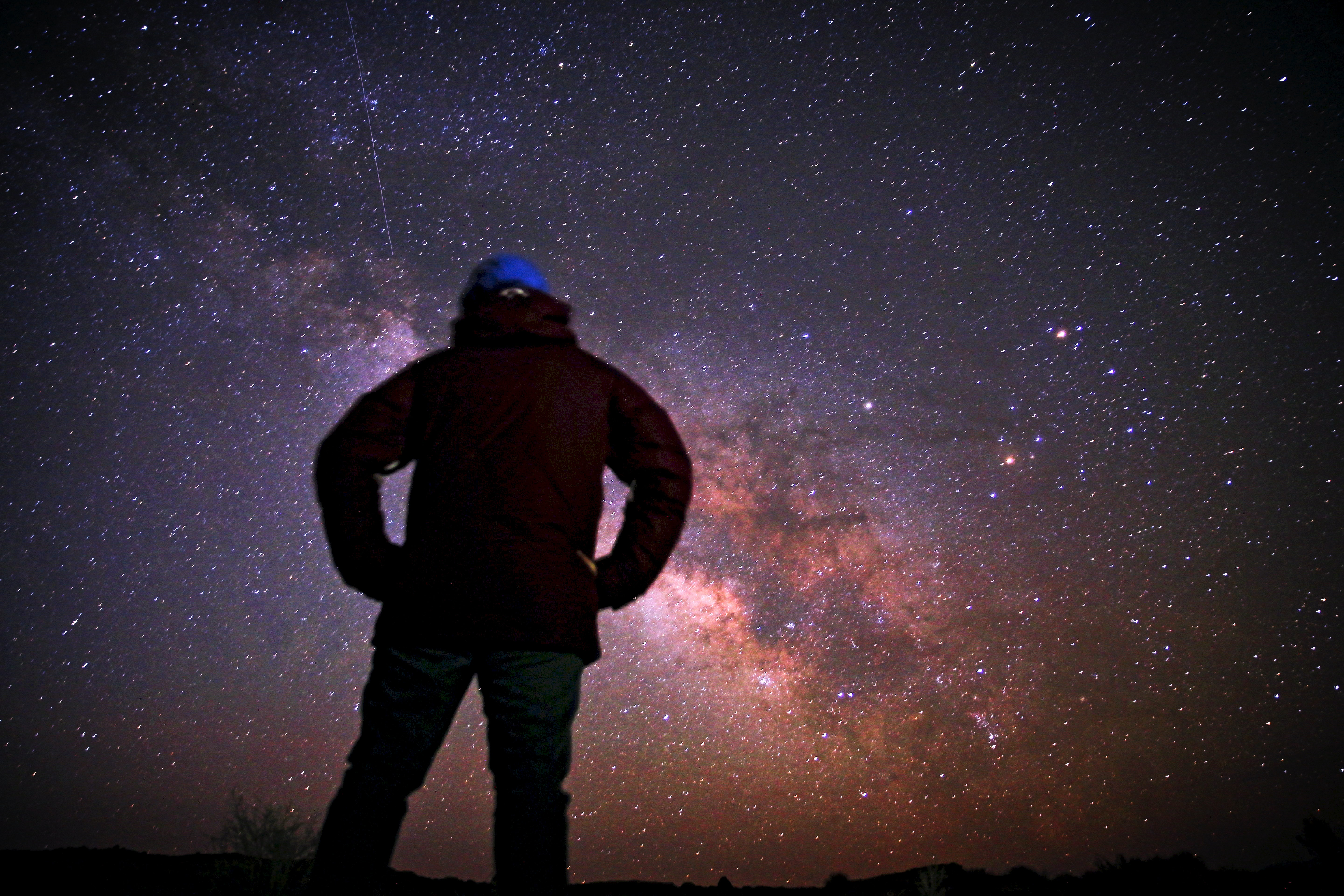 A man looking up at the Milky Way and stars at Goblin Valley Road.