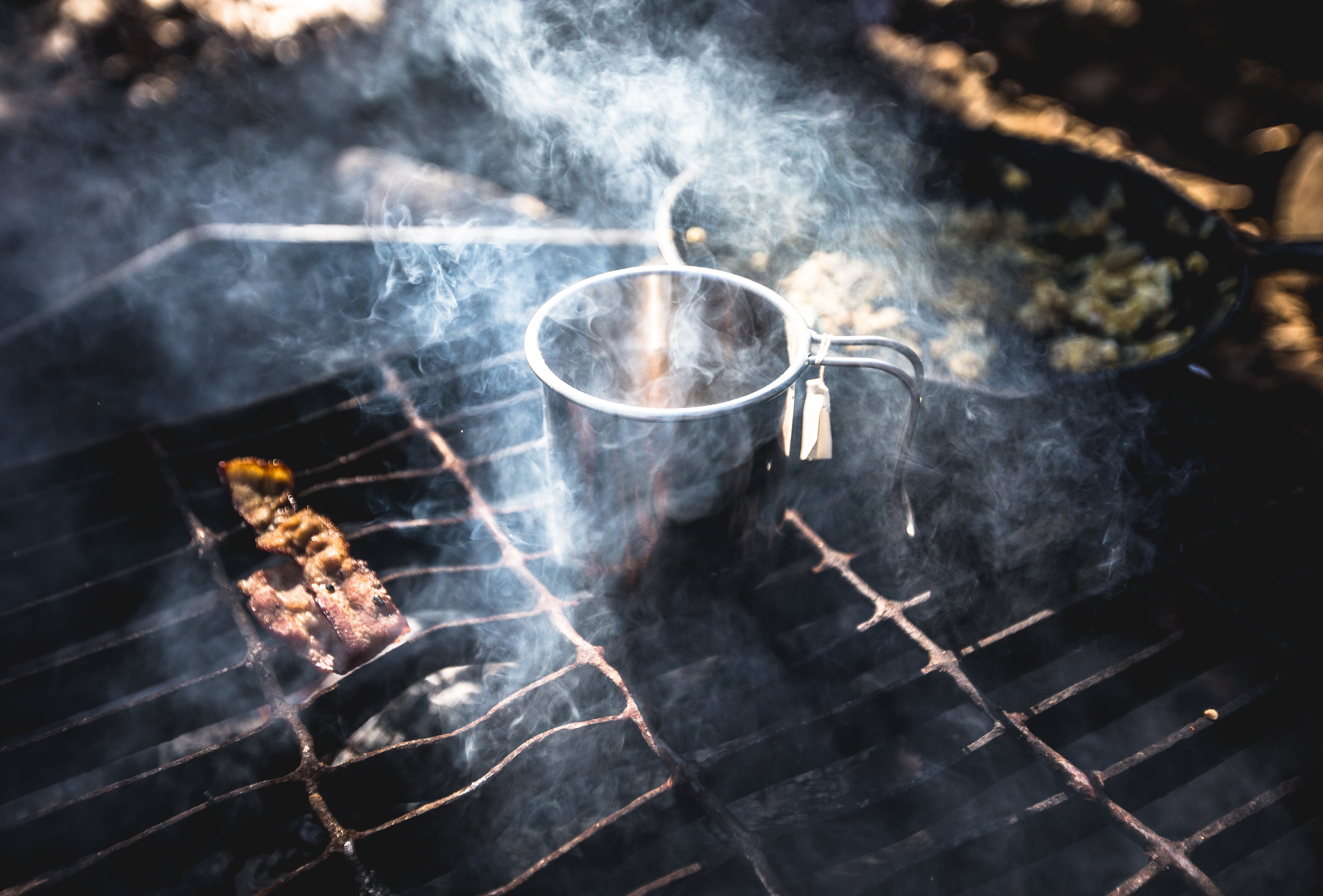 A pan and a mug on an outdoor grill with smoke rising above