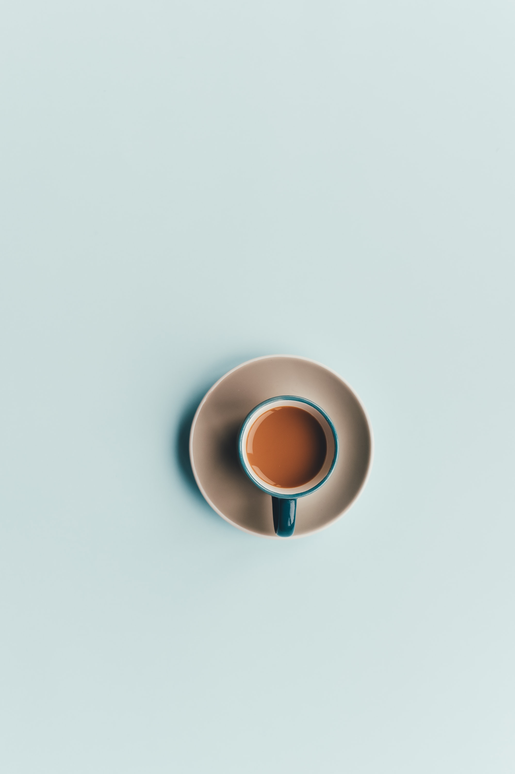 An overhead shot of coffee in a blue cup on a white saucer