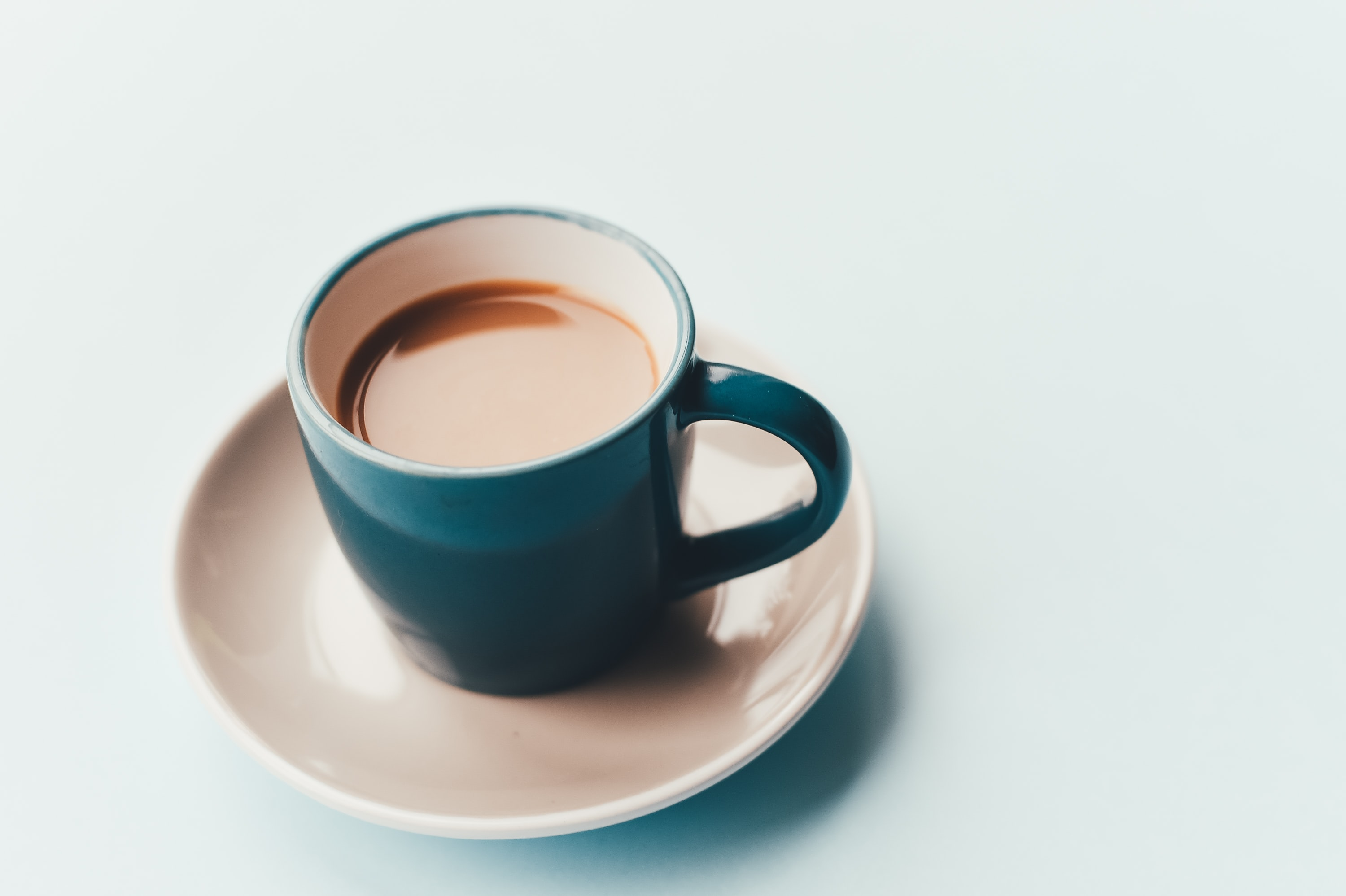 A blue cup with coffee on a white saucer