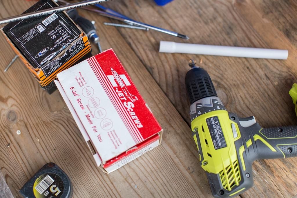 green Ryobi hand drill near white and red box
