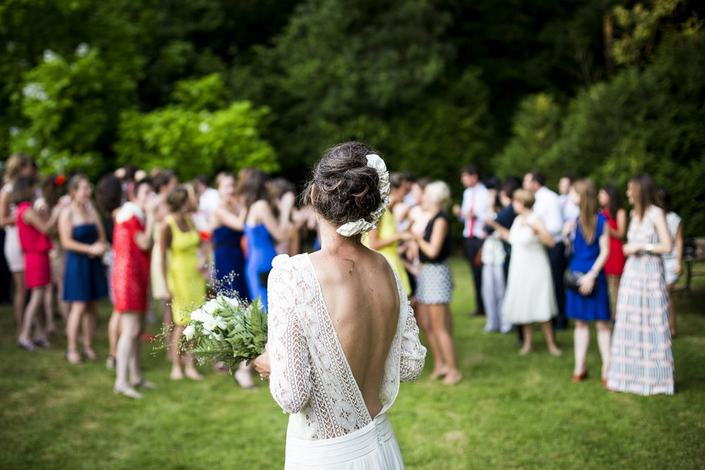 woman wearing wedding dress standing in front of crowd during daytime