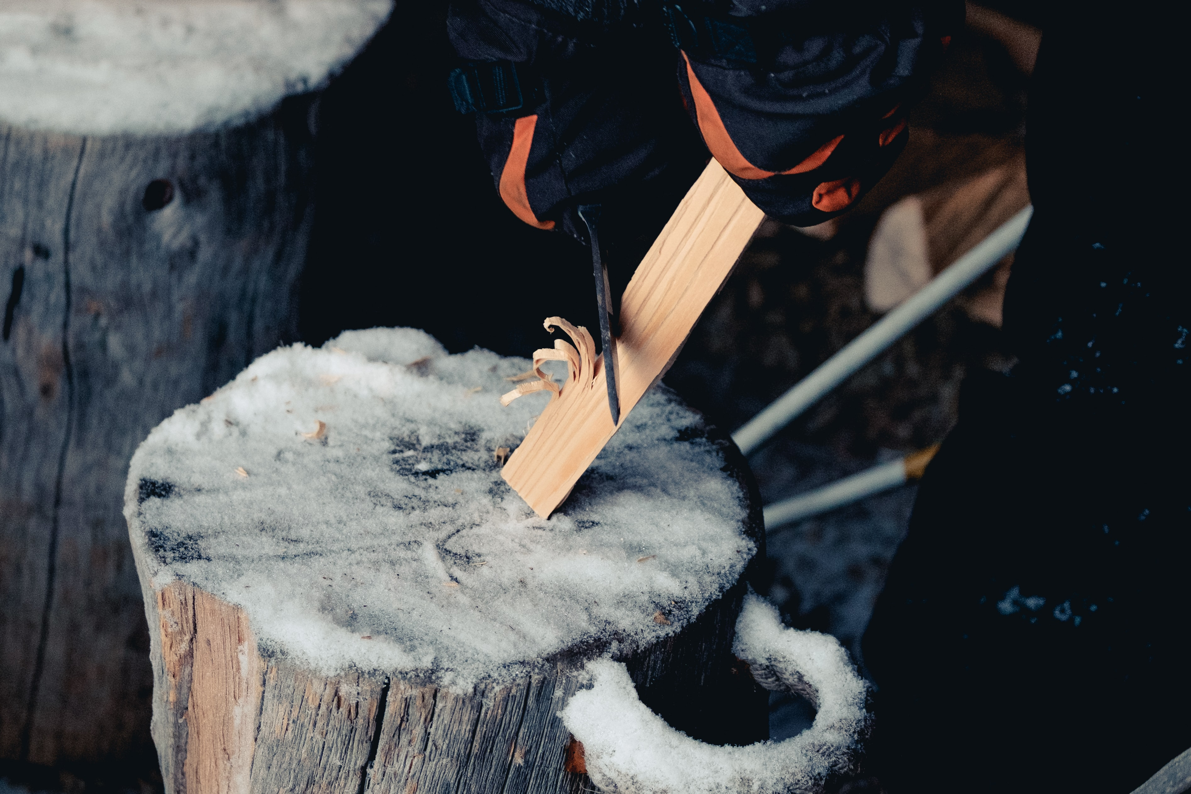 Man cuts wood on a snowy stump in Rukatunturi