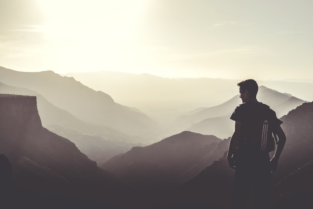 man standing on top of the mountain during daytime