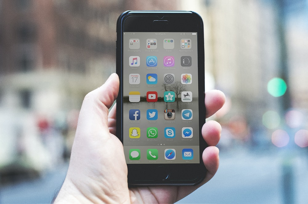 person holding a space gray iPhone 6 and black case