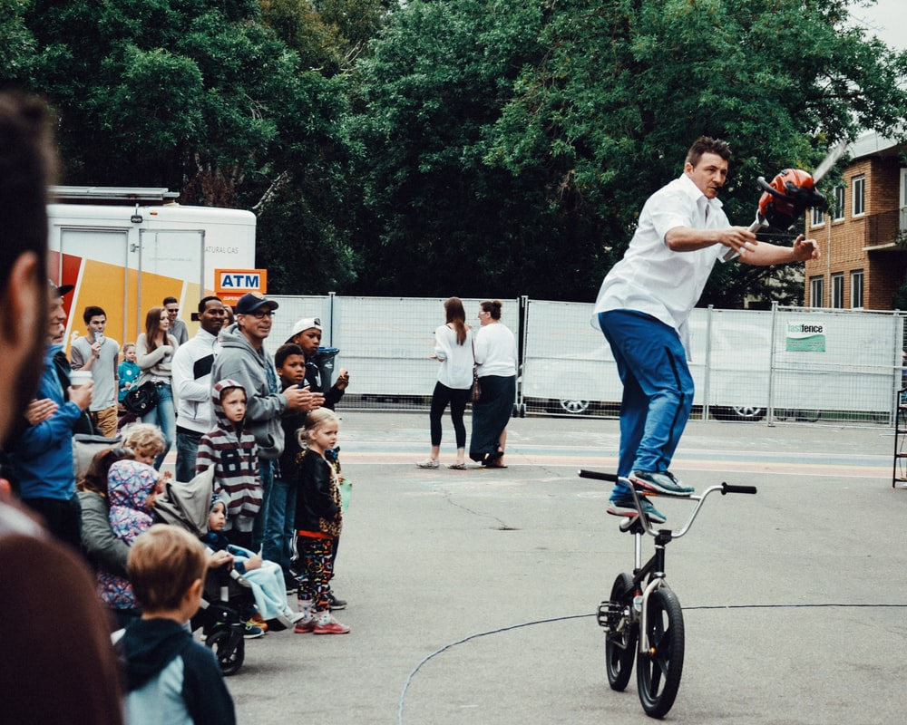 man standing on BMX bike