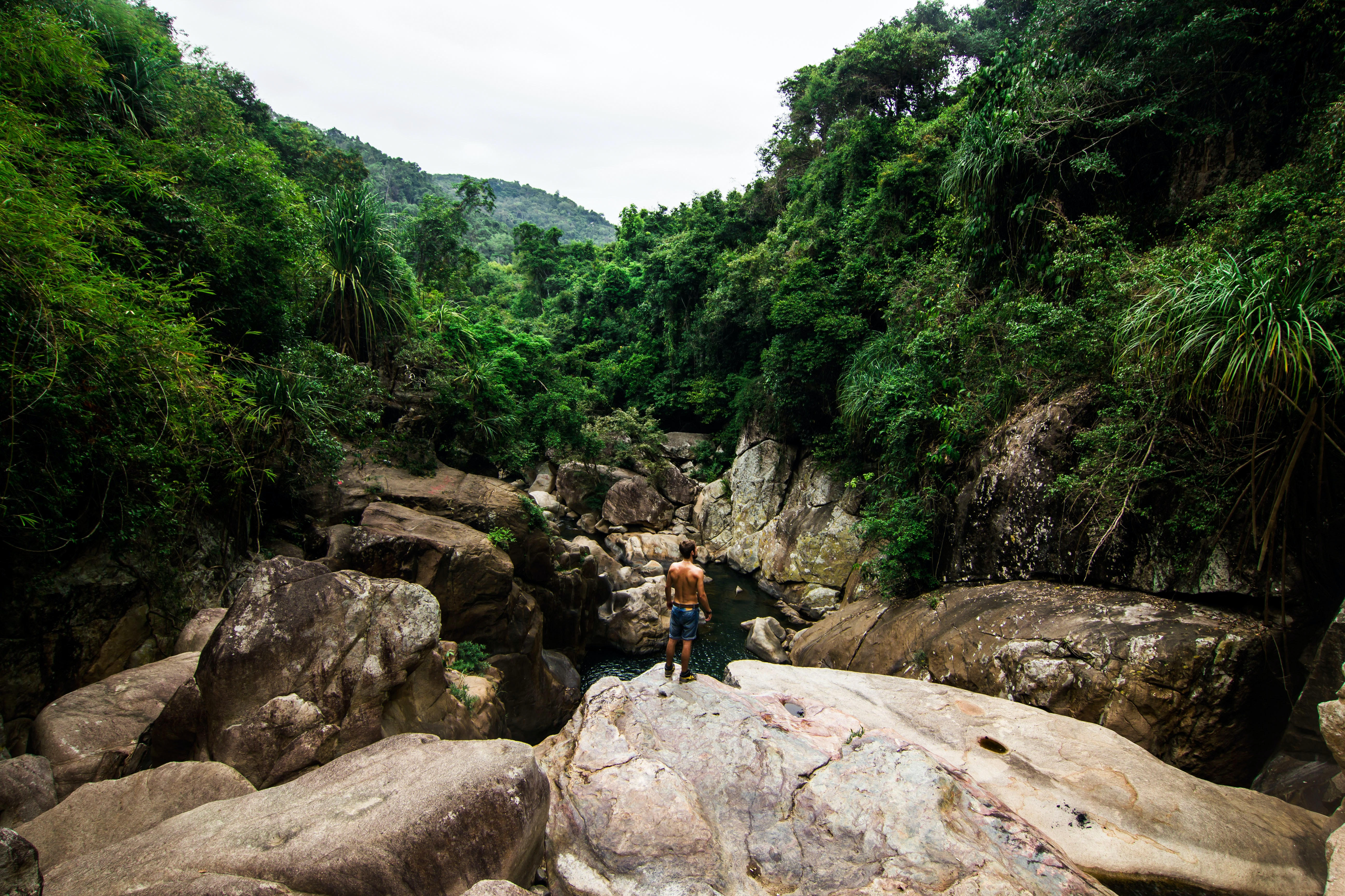 A shirtless man on smooth rocks overlooking a river in Vietnam
