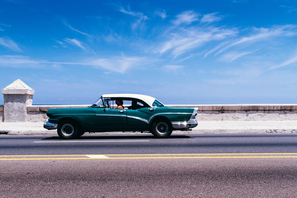 green coupe on gray asphalt road