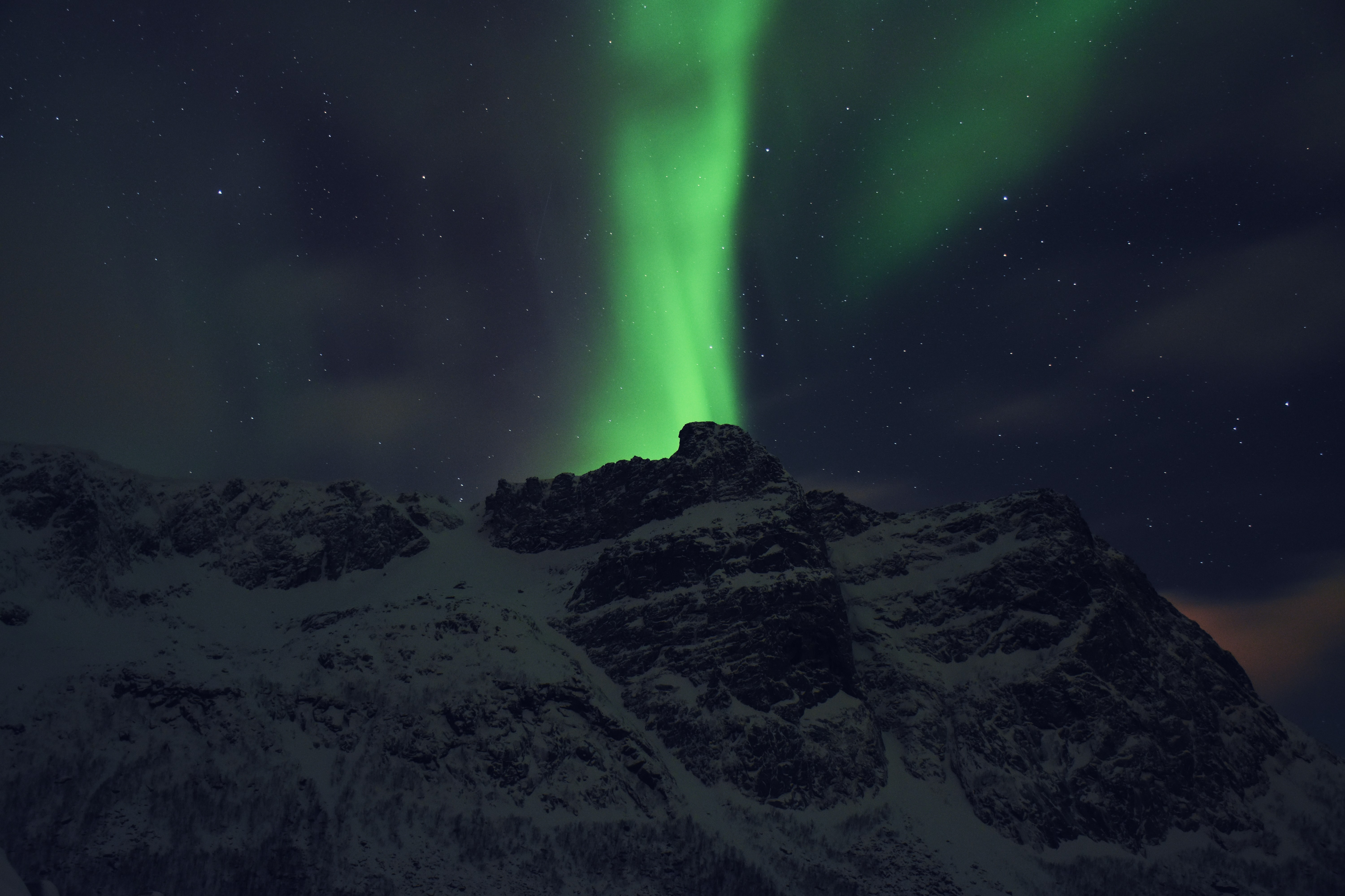 Green Northern Lights rises above snow covered mountains in Tromsø