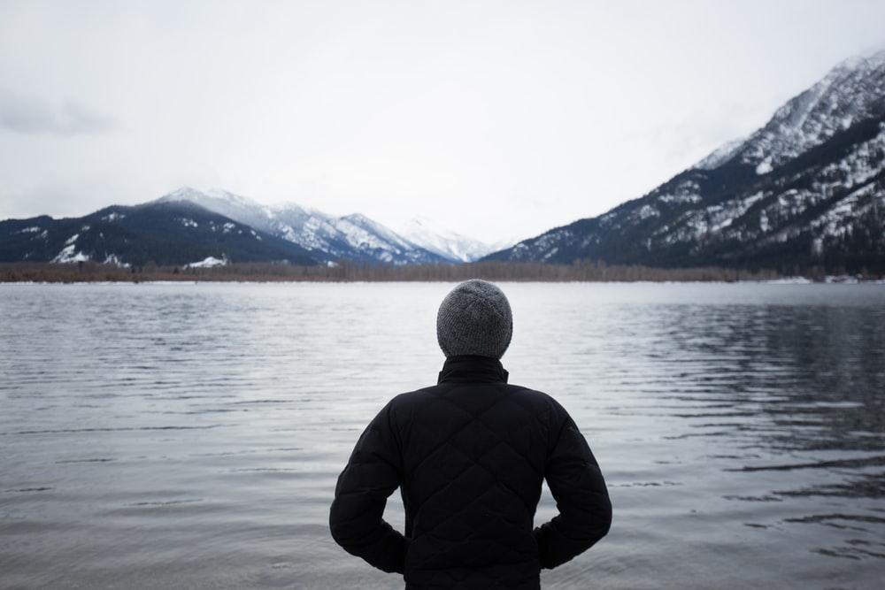 man in black top standing in front of lake
