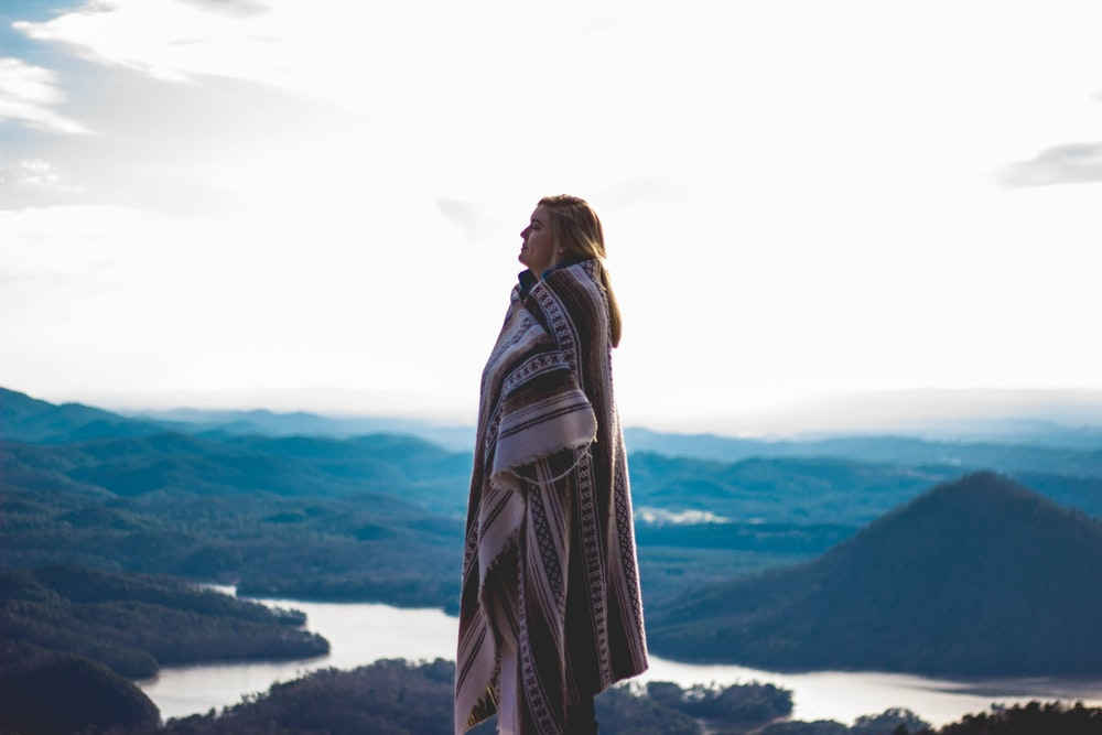 woman wearing coat standing on cliff