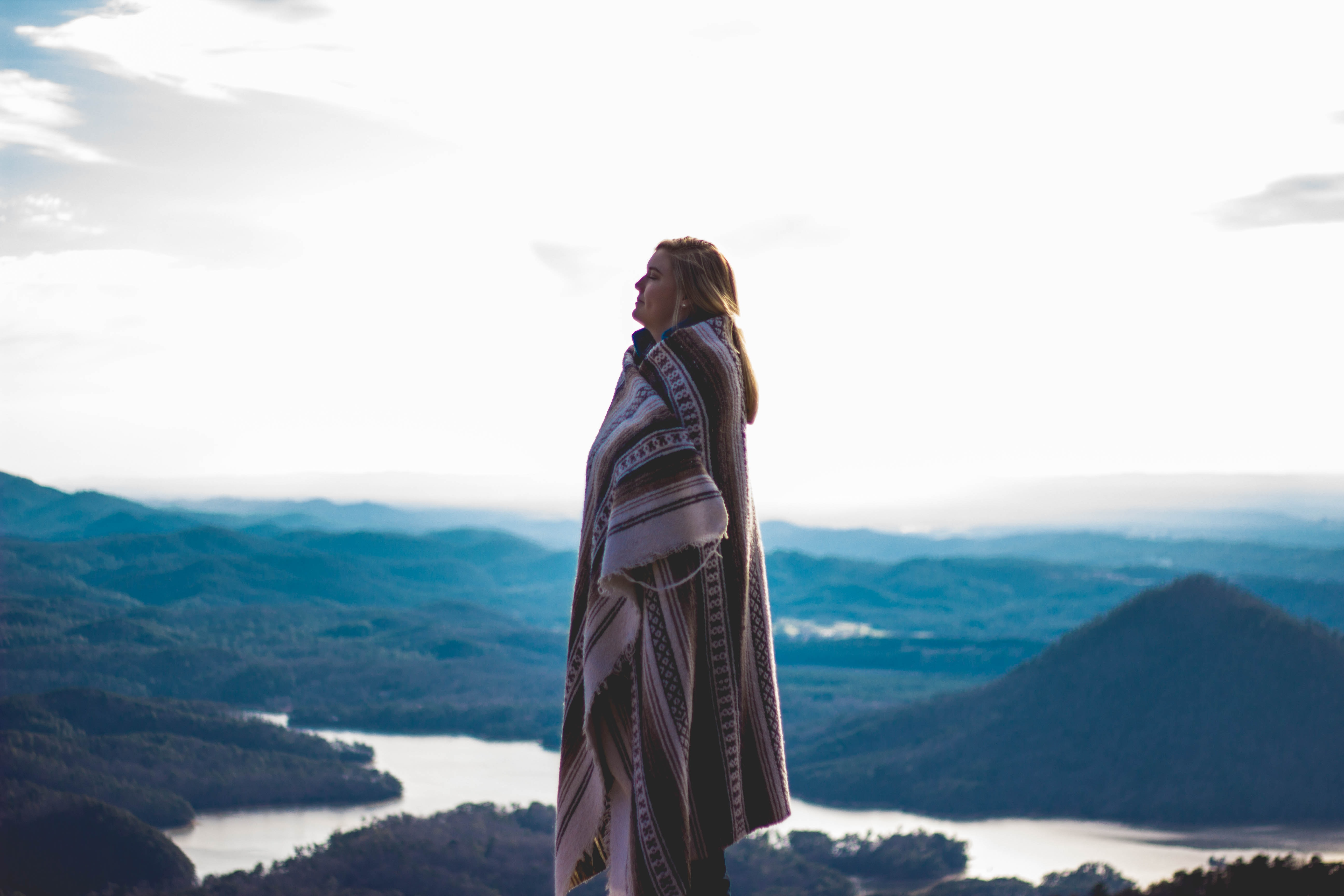 Person wrapped up in an oversized blanket shawl near the mountains