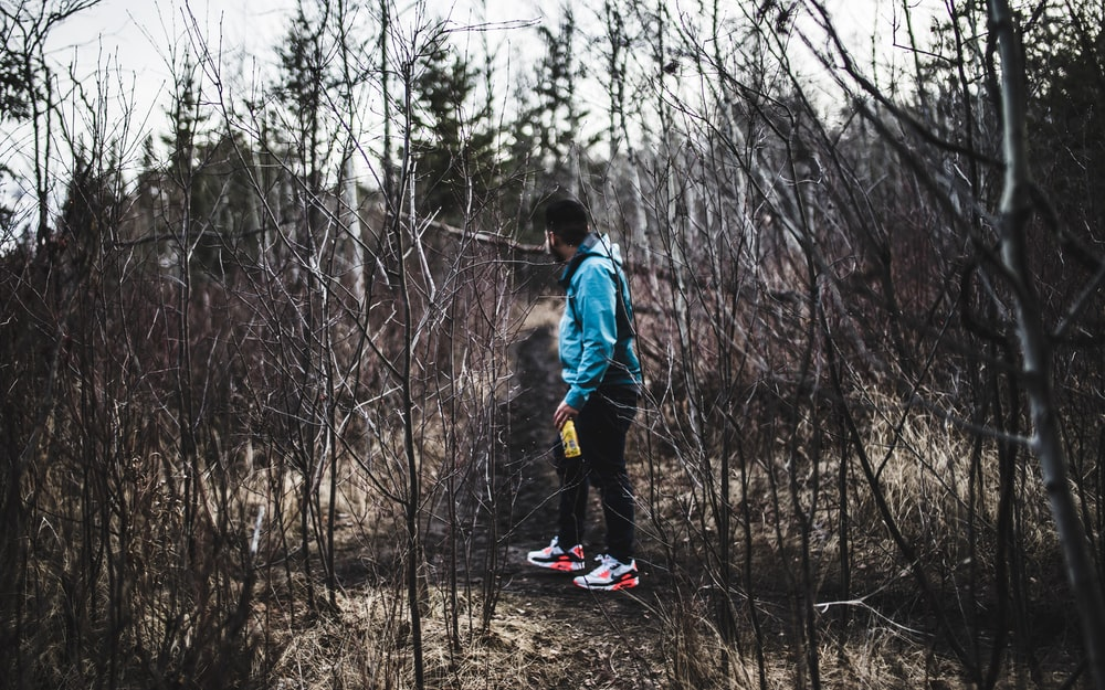 man in blue jacket and black pants in woods