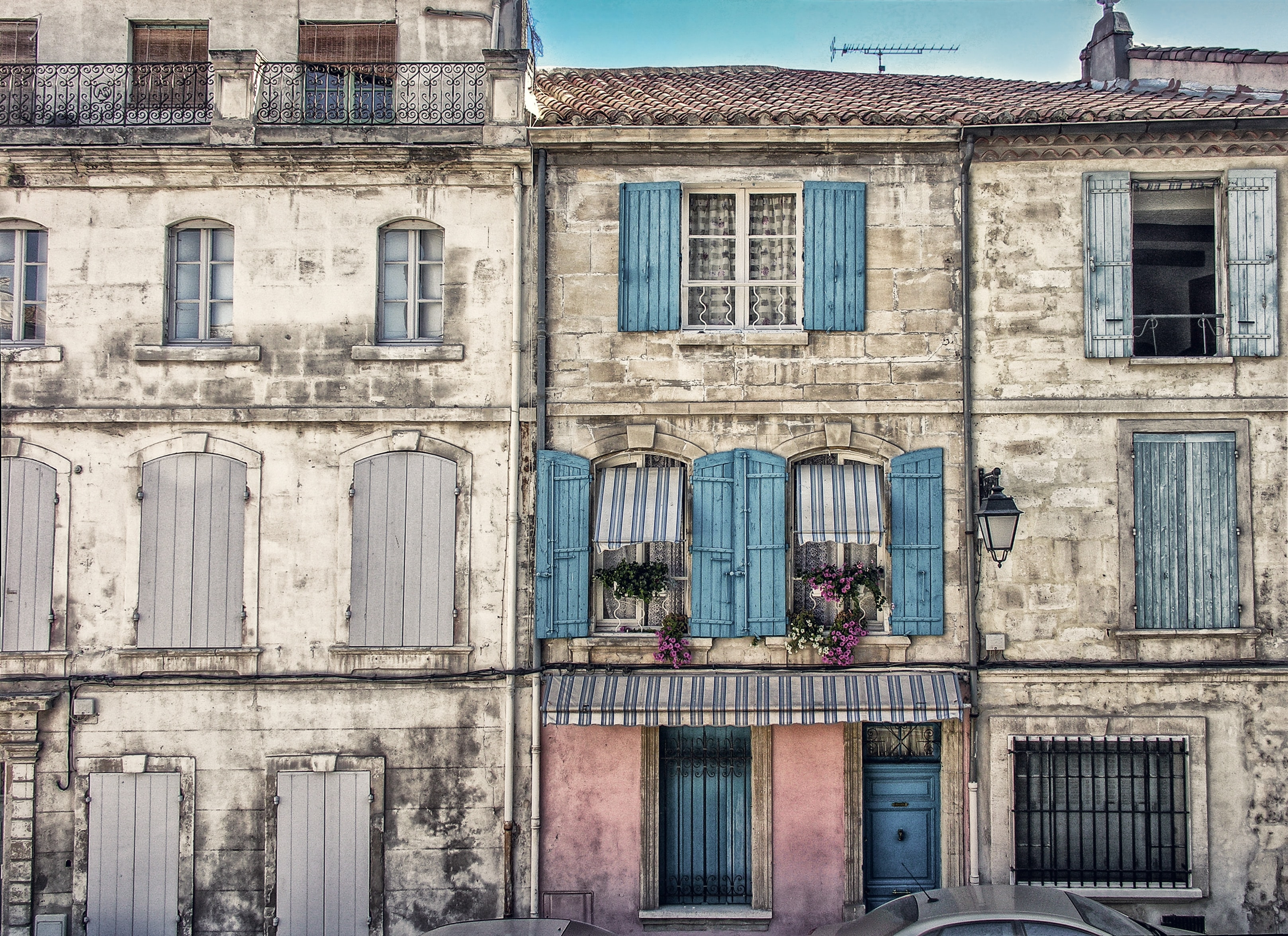 Two old buildings constructed together having wooden and glass windows with flowers on some in arles.