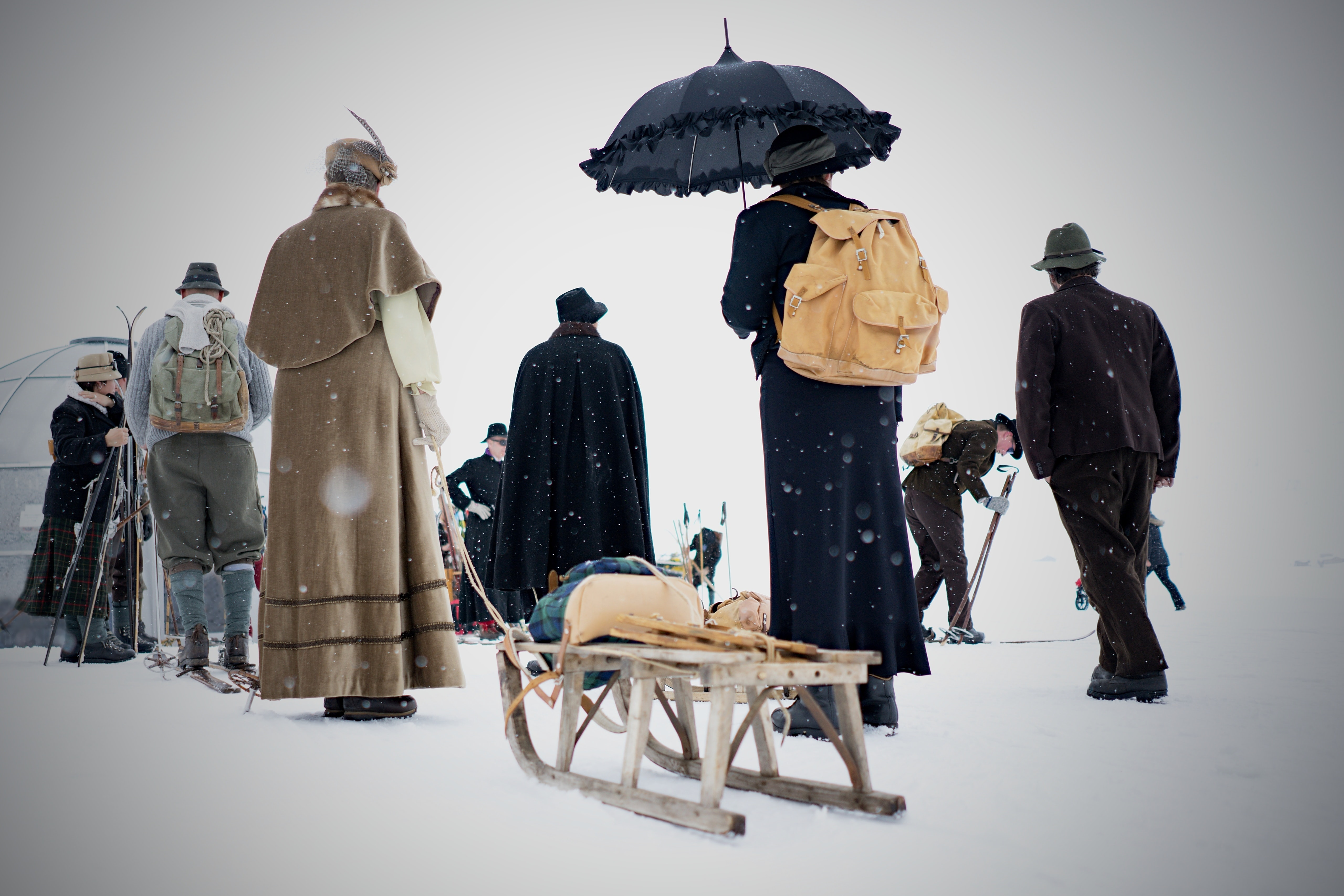 People in coats with a sled, skies, an umbrella and backpacks are traveling through snowfall