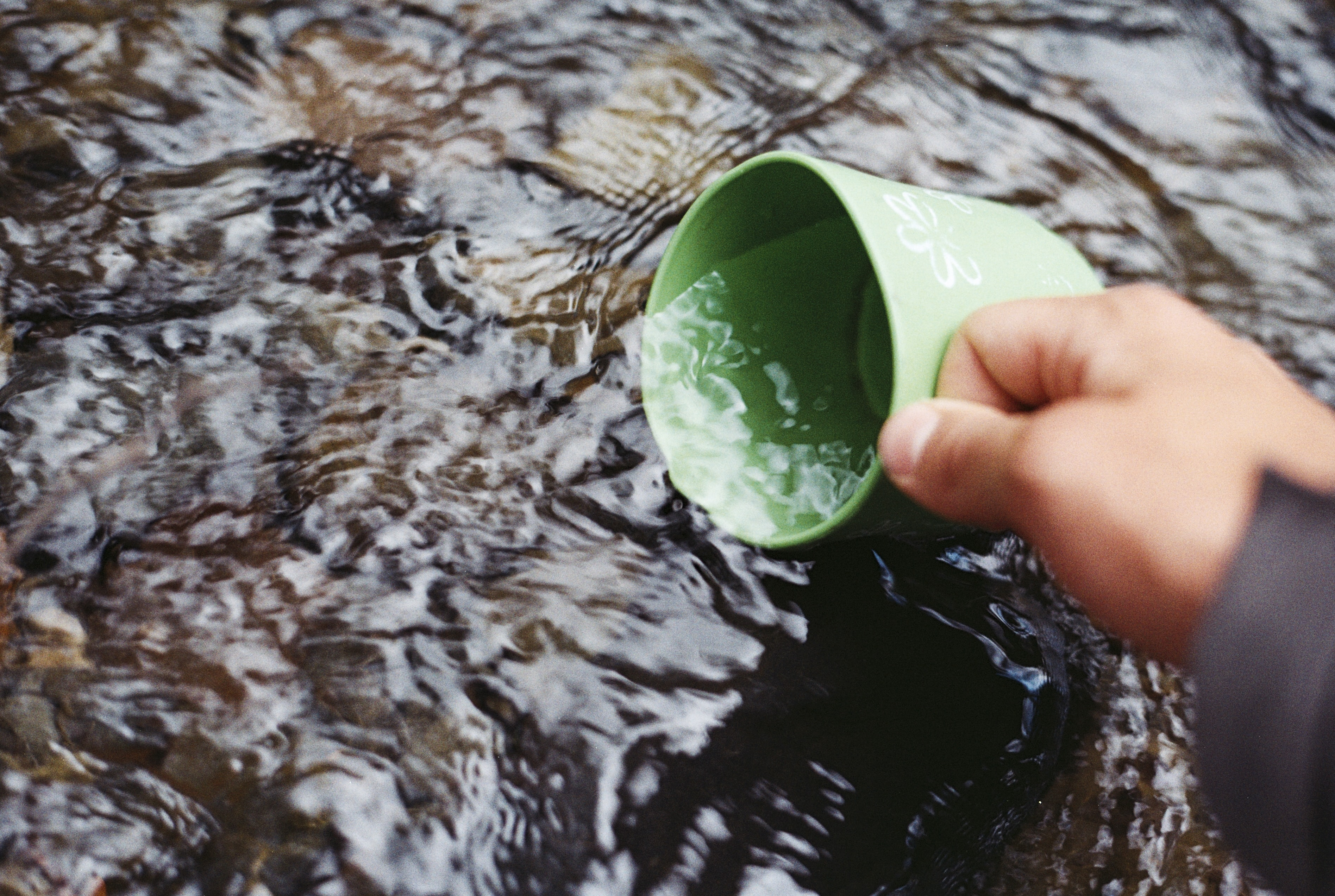 A person filling up a green mug in a river in Torres del Paine National Park