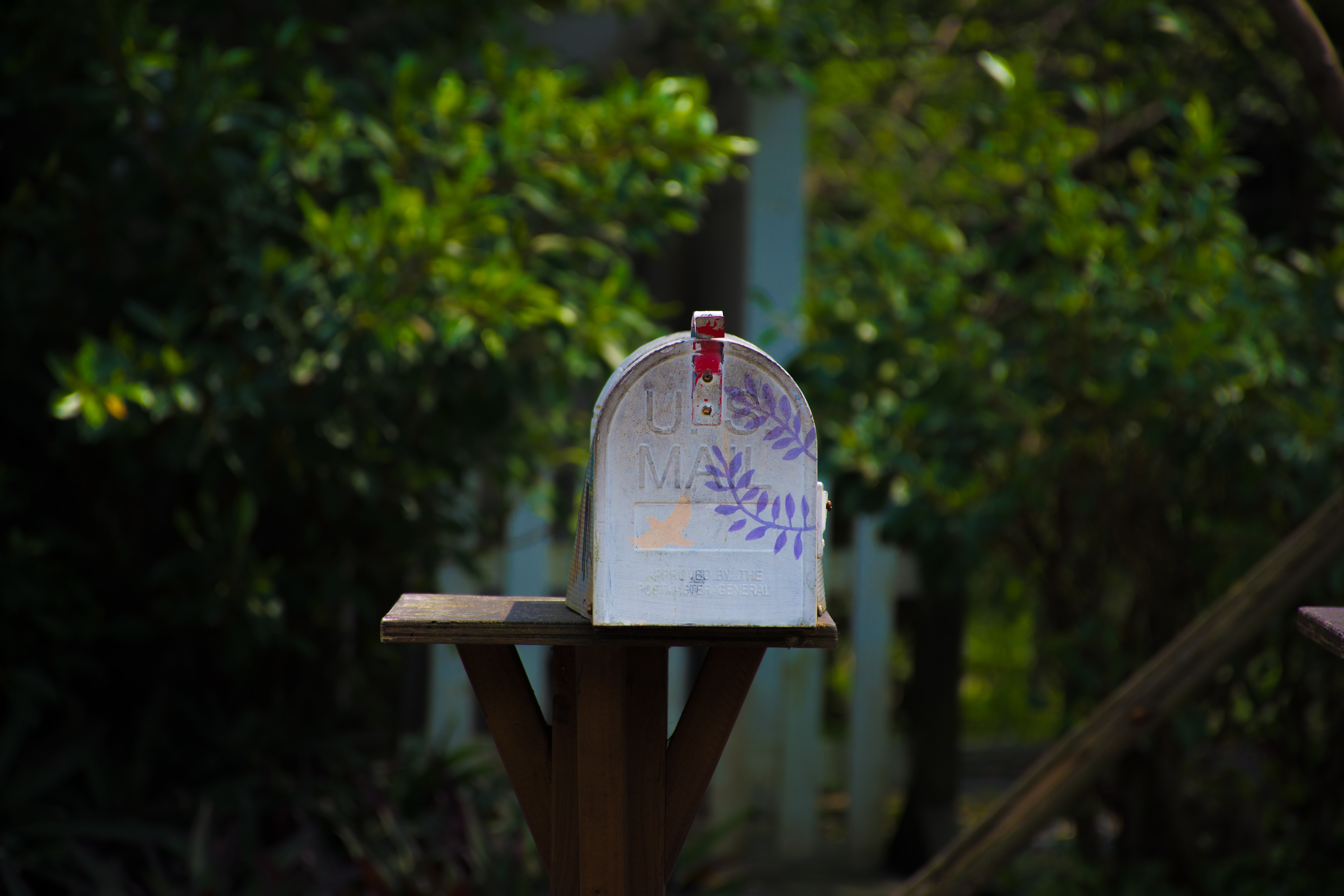 Hand-painted mailbox resting on a wooden pedestal