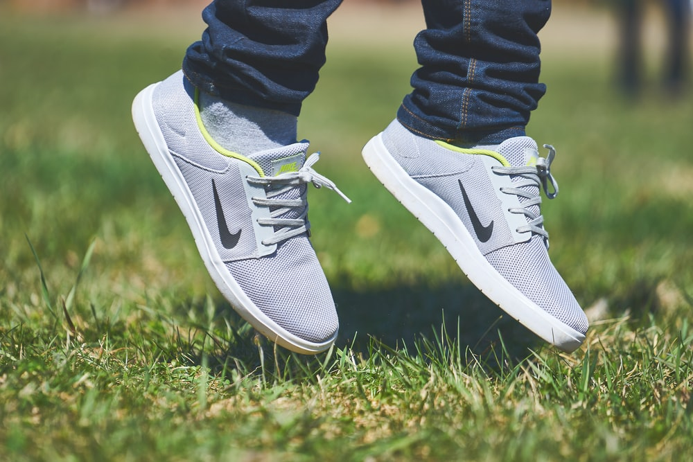 pair of gray Nike low-top sneakers hanging on green grass
