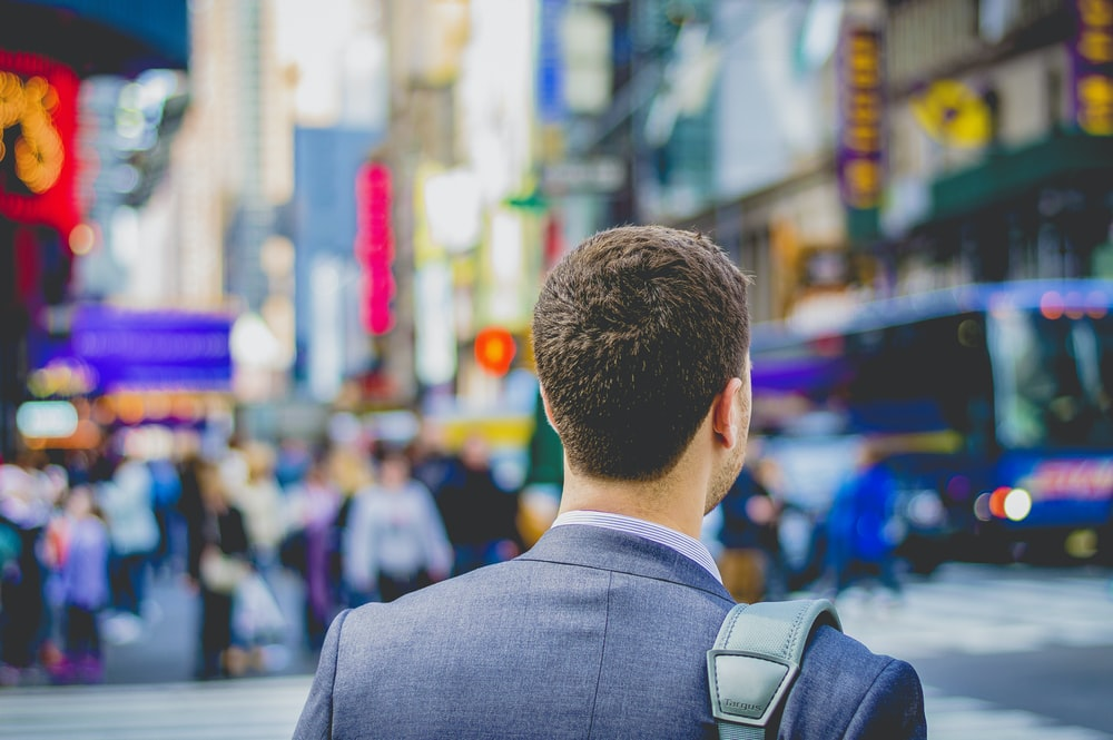 shallow focus photography of man in suit jacket's back