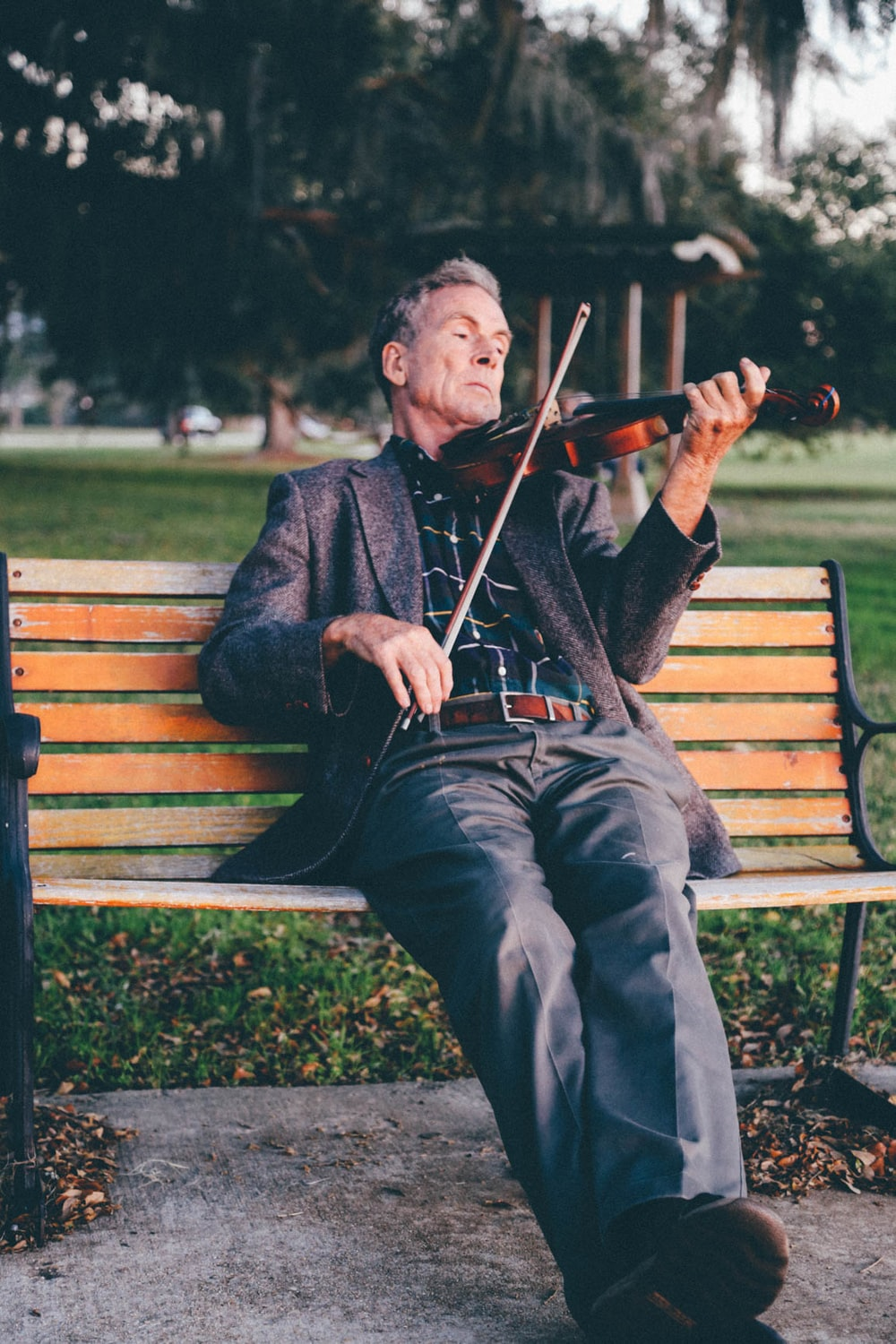 An older man playing a violin on a park bench.