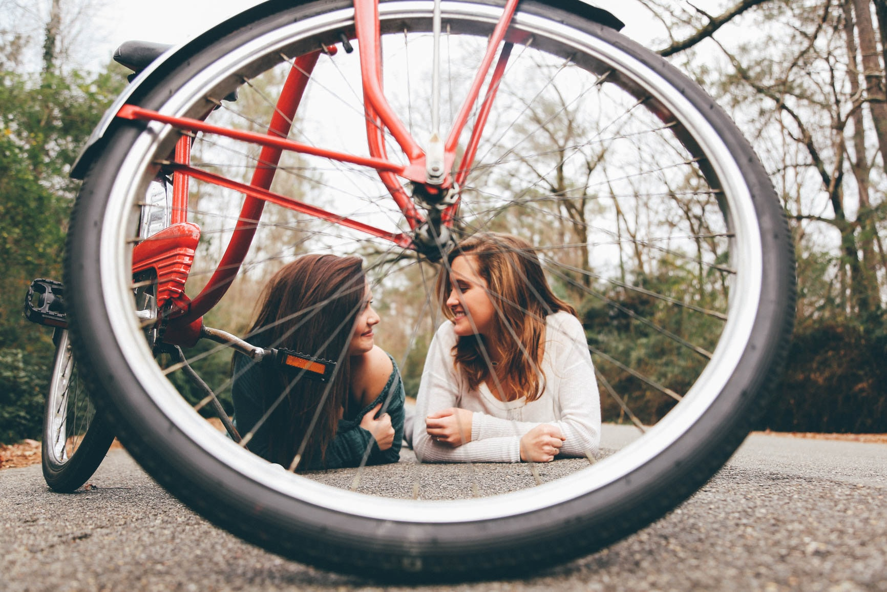 Two girls laying on a sidewalk, seen through the wheel of a parked bike