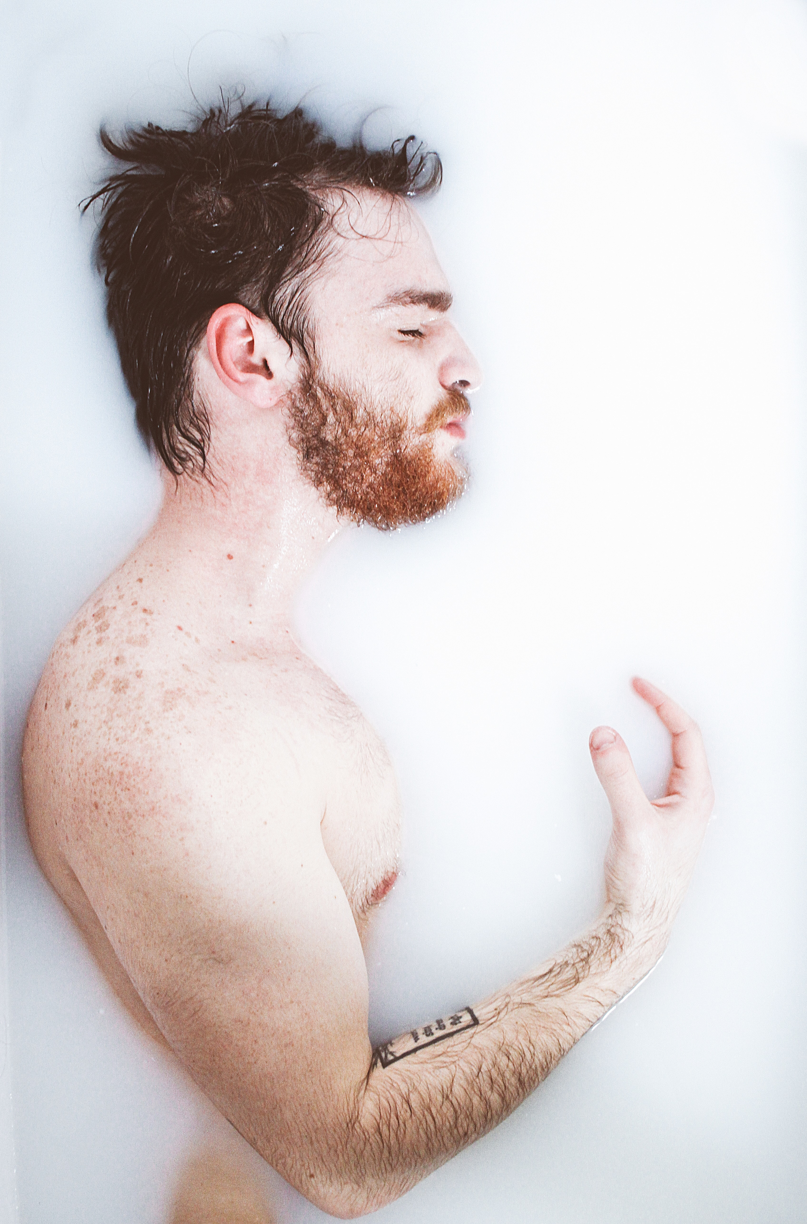 A shirtless bearded man holding his hand up.