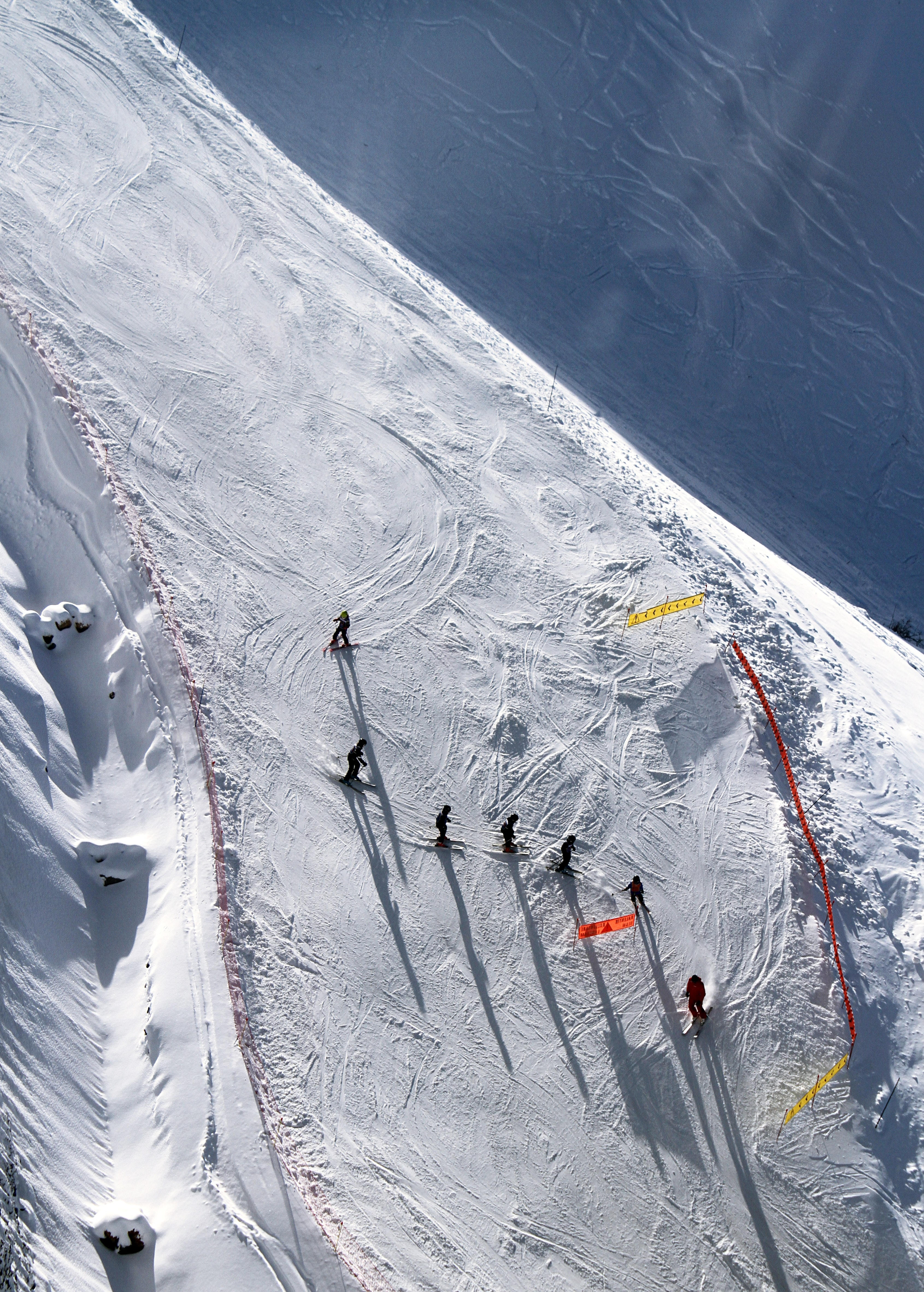 A drone shot directly above seven skiers preparing for a slope race