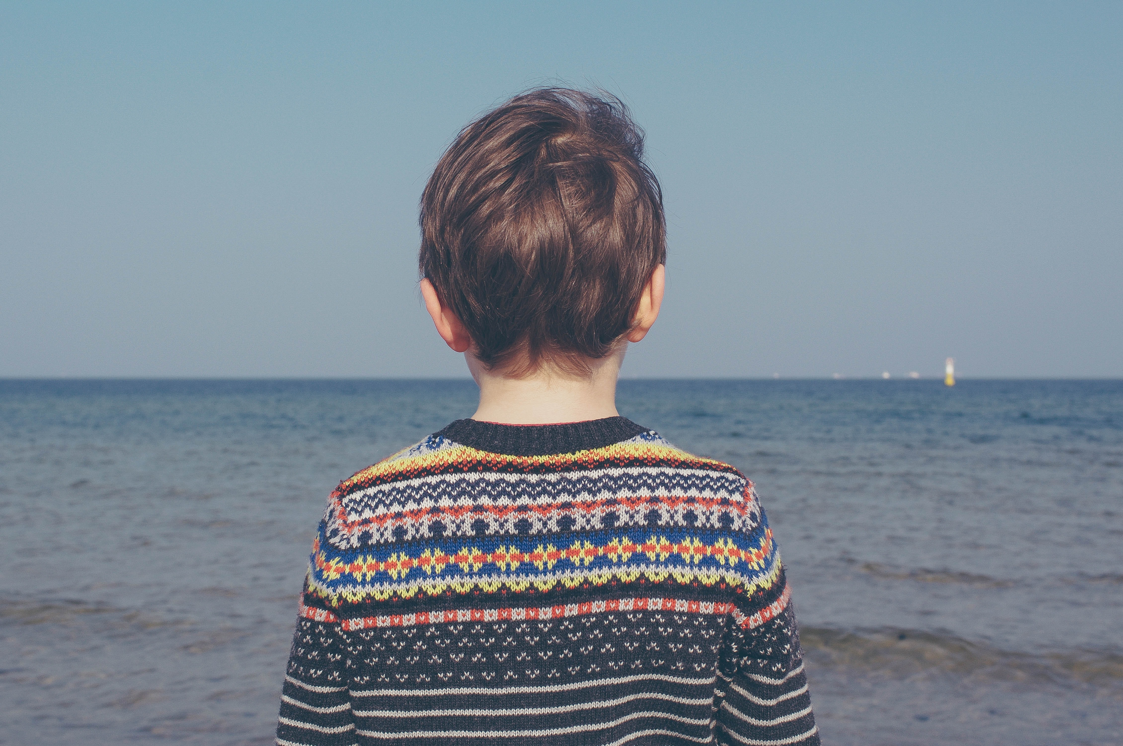person wearing multicolored striped floral sweater facing the sea
