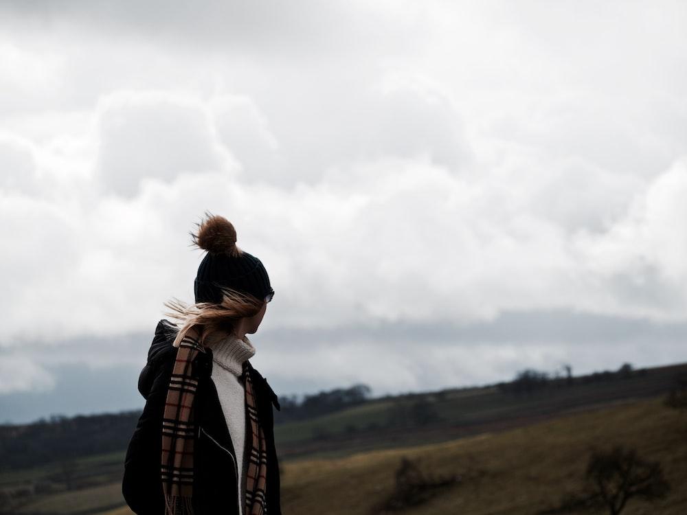 woman looking at back under nimbus clouds